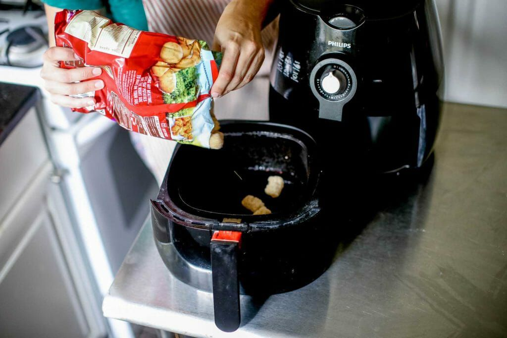 Pouring food into an air fryer