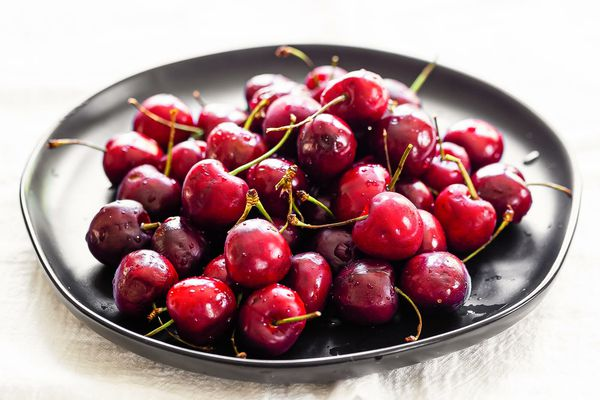 A dark plate of bing cherries piled in the center to show how to pick cherries.