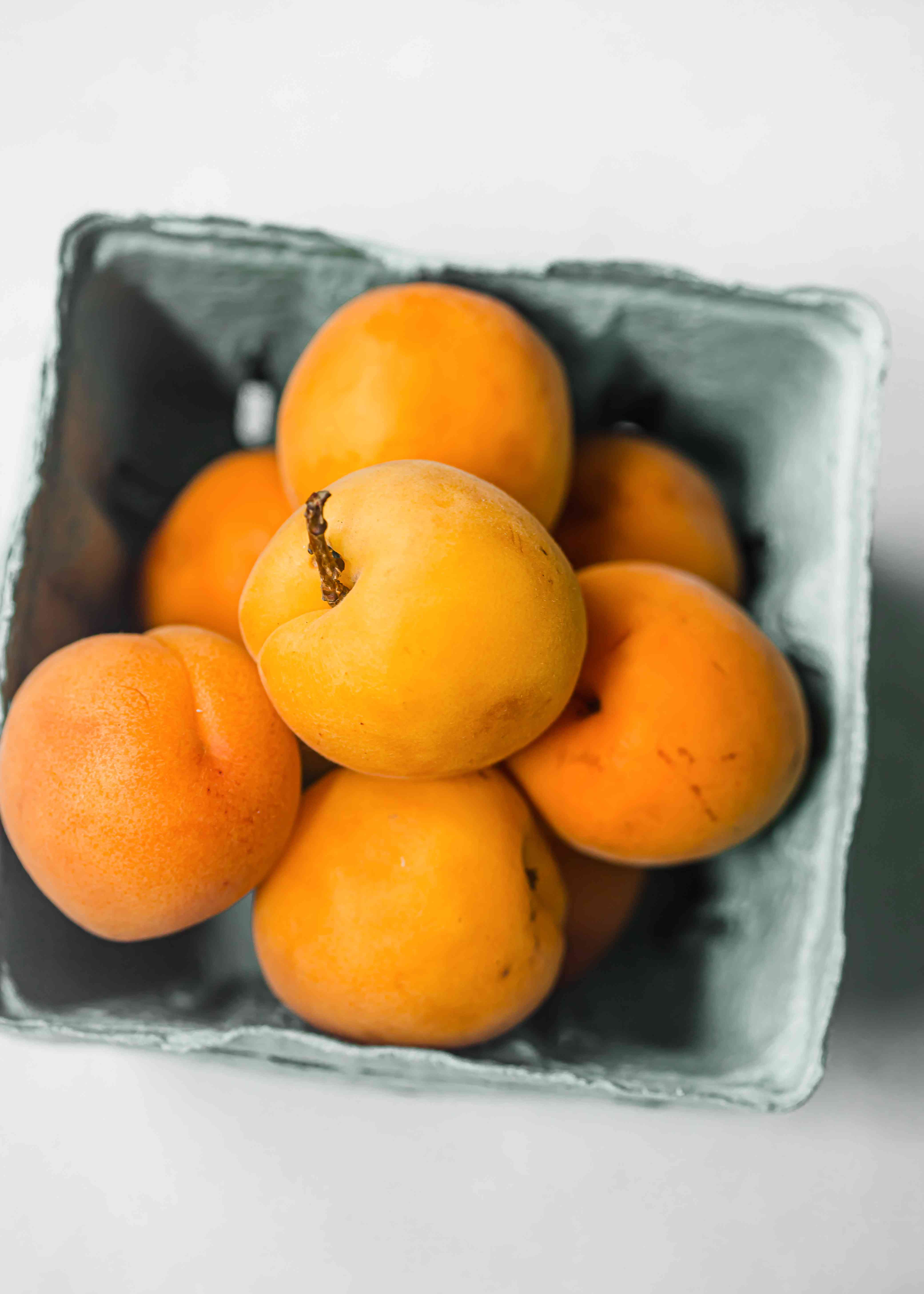 Apricots in a blue gray cardboard pint container