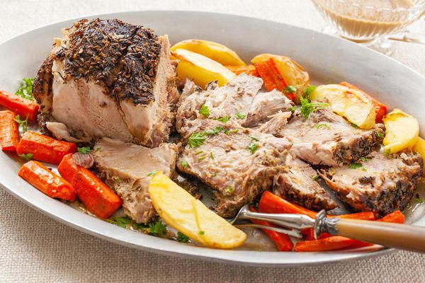 A platter with pork shoulder, carrots and potatoes.