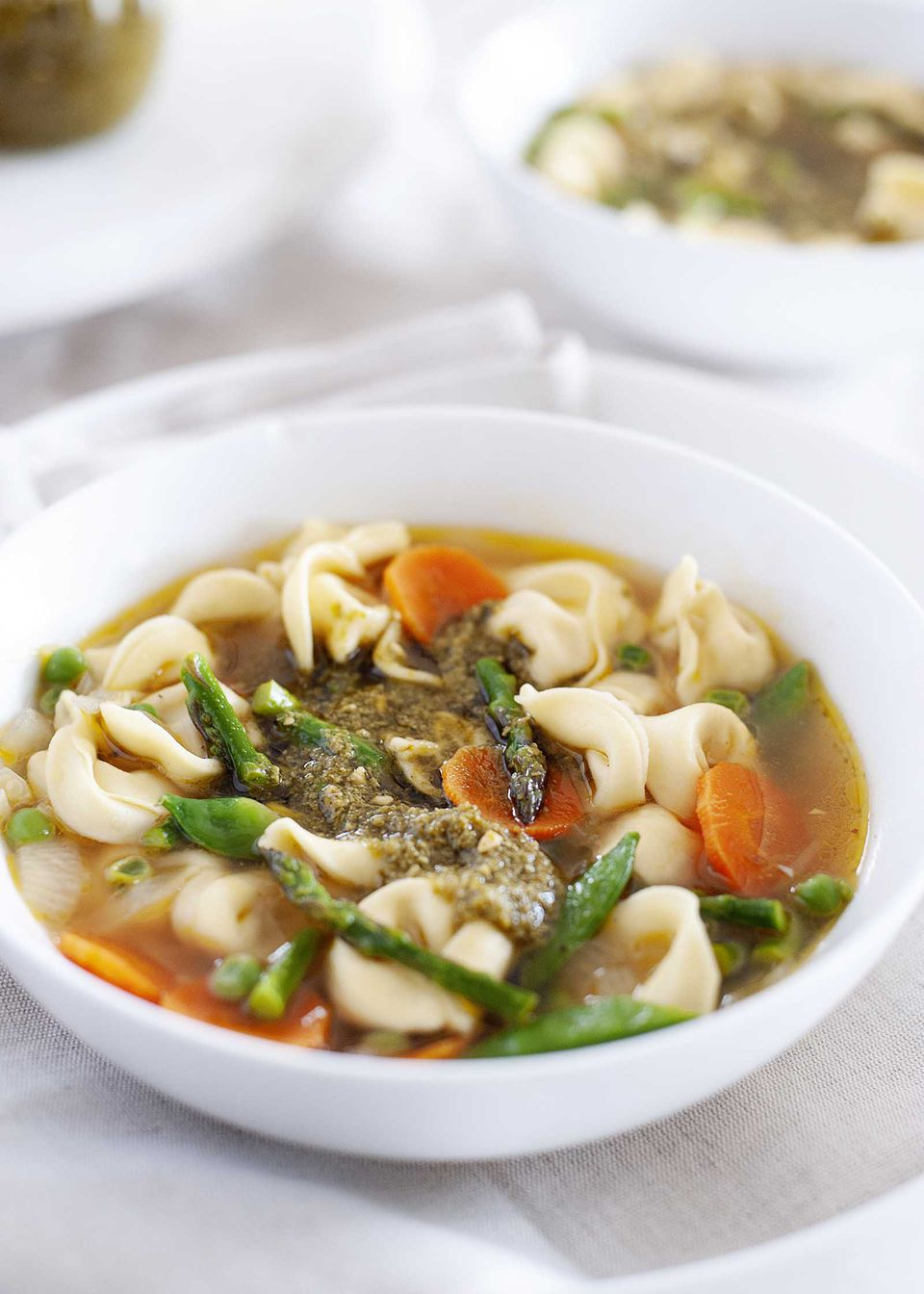 Bowl of vegetarian soup with tortellini in a white bowl on a table with a second bowl in the background. Chopped asparagus, sliced carrots and pesto are visible with the tortellini.