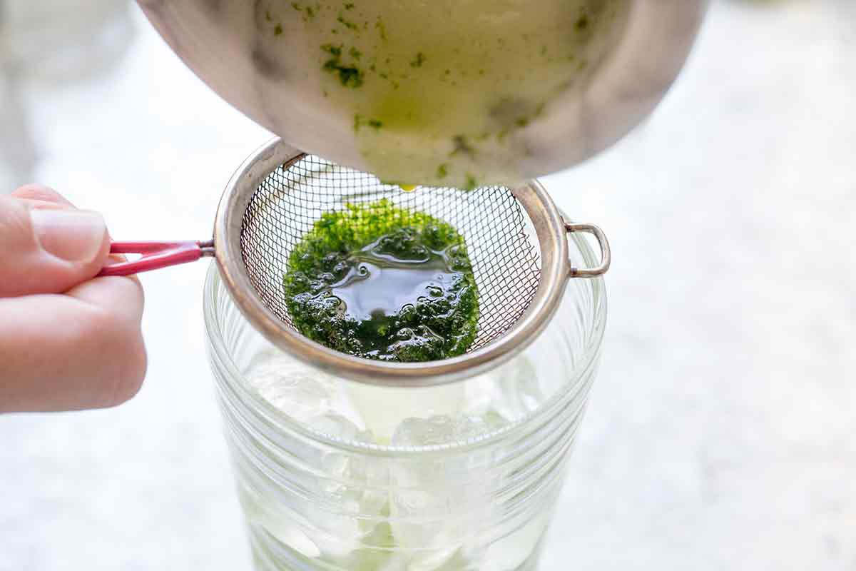 Strain the mint and rum mixture for mojitos into a glass