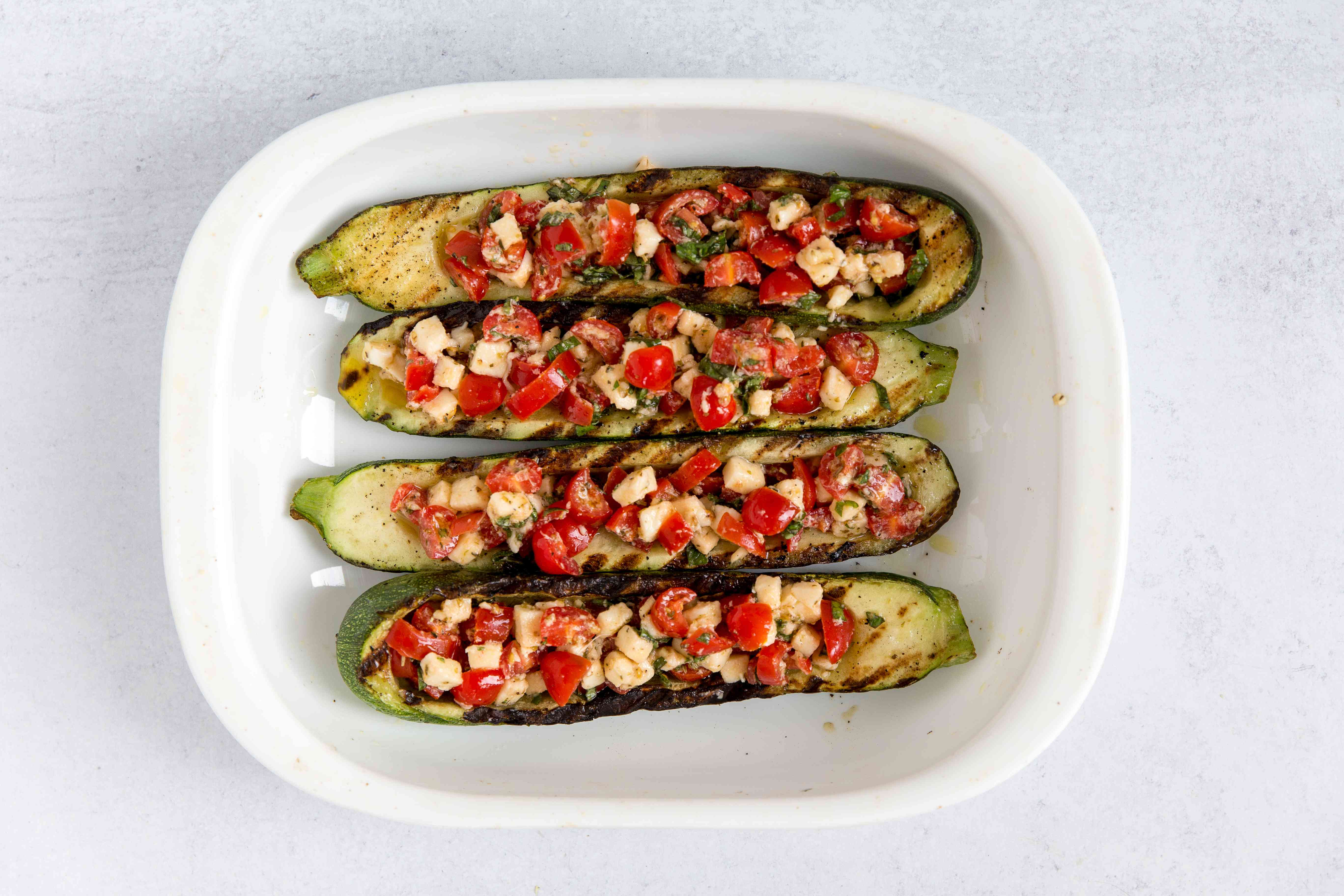 Zucchini boats filled with filling to make grilled zucchini stuffed with tomatoes, mozzarella, and basil.