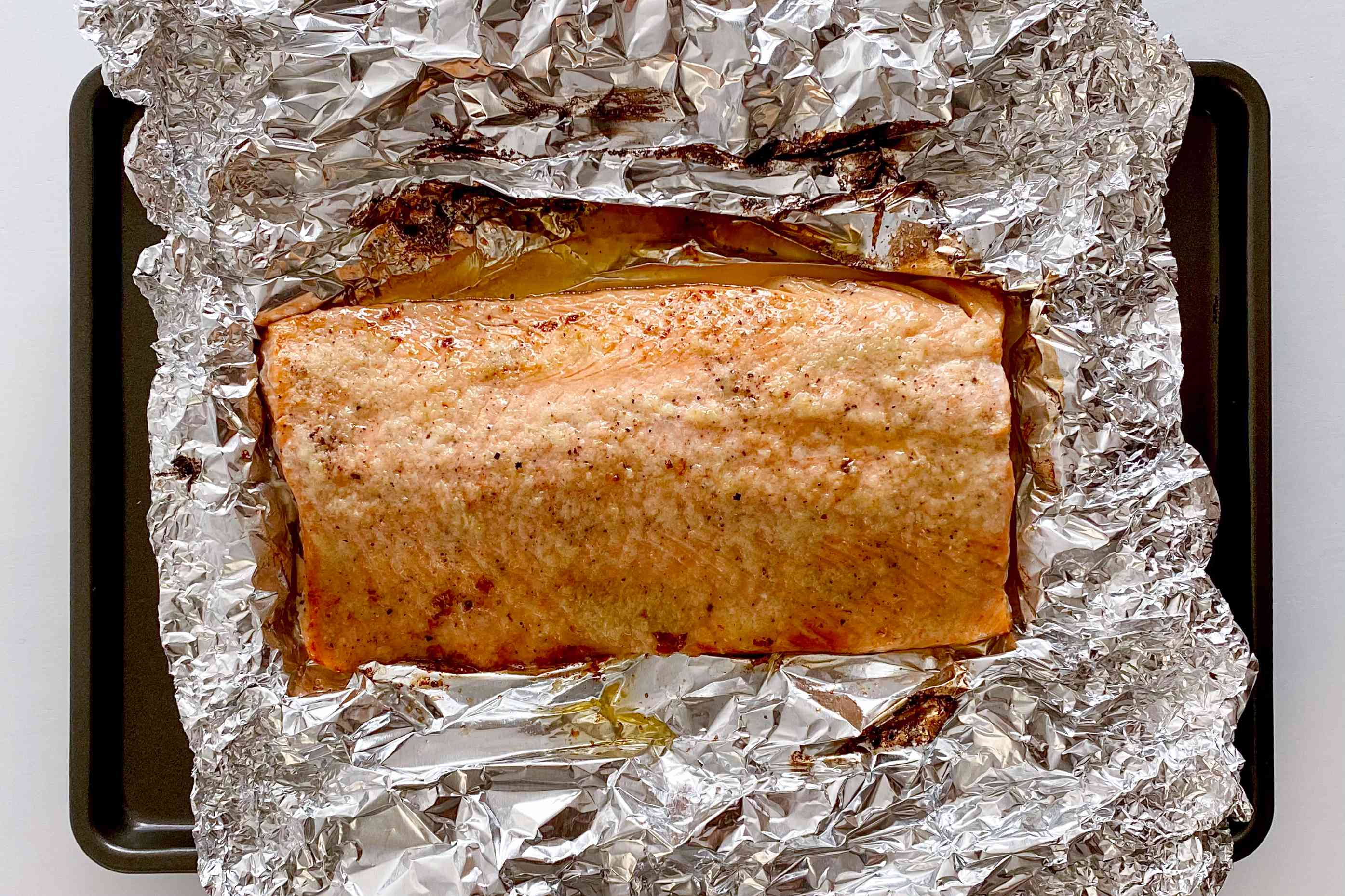 Honey Garlic Butter Roasted Salmon out of the oven and resting in the foil it was baked in.