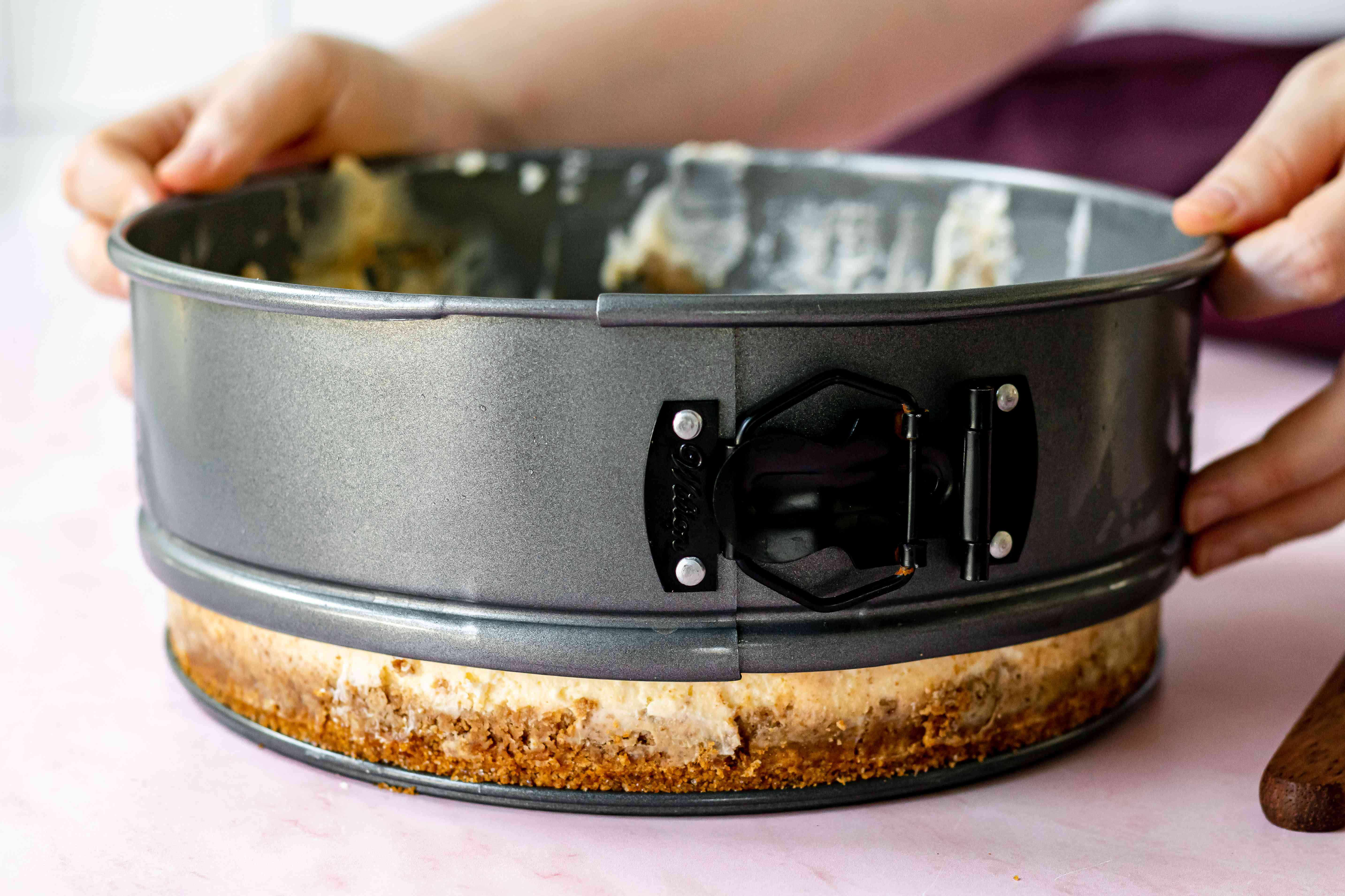 Releasing the cheesecake from the pan.