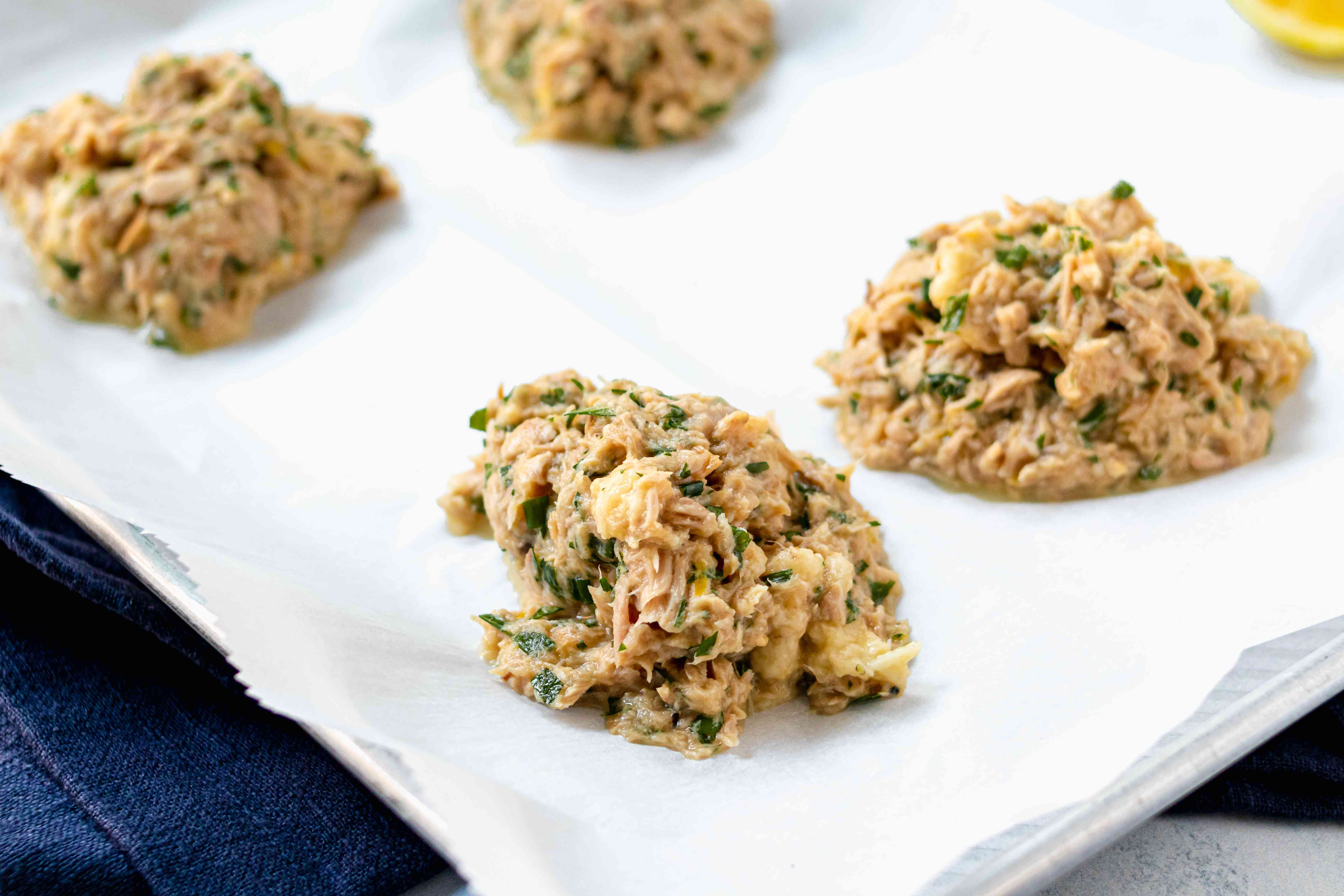 Tuna patties scooped on parchment paper to show how to make tuna fish.