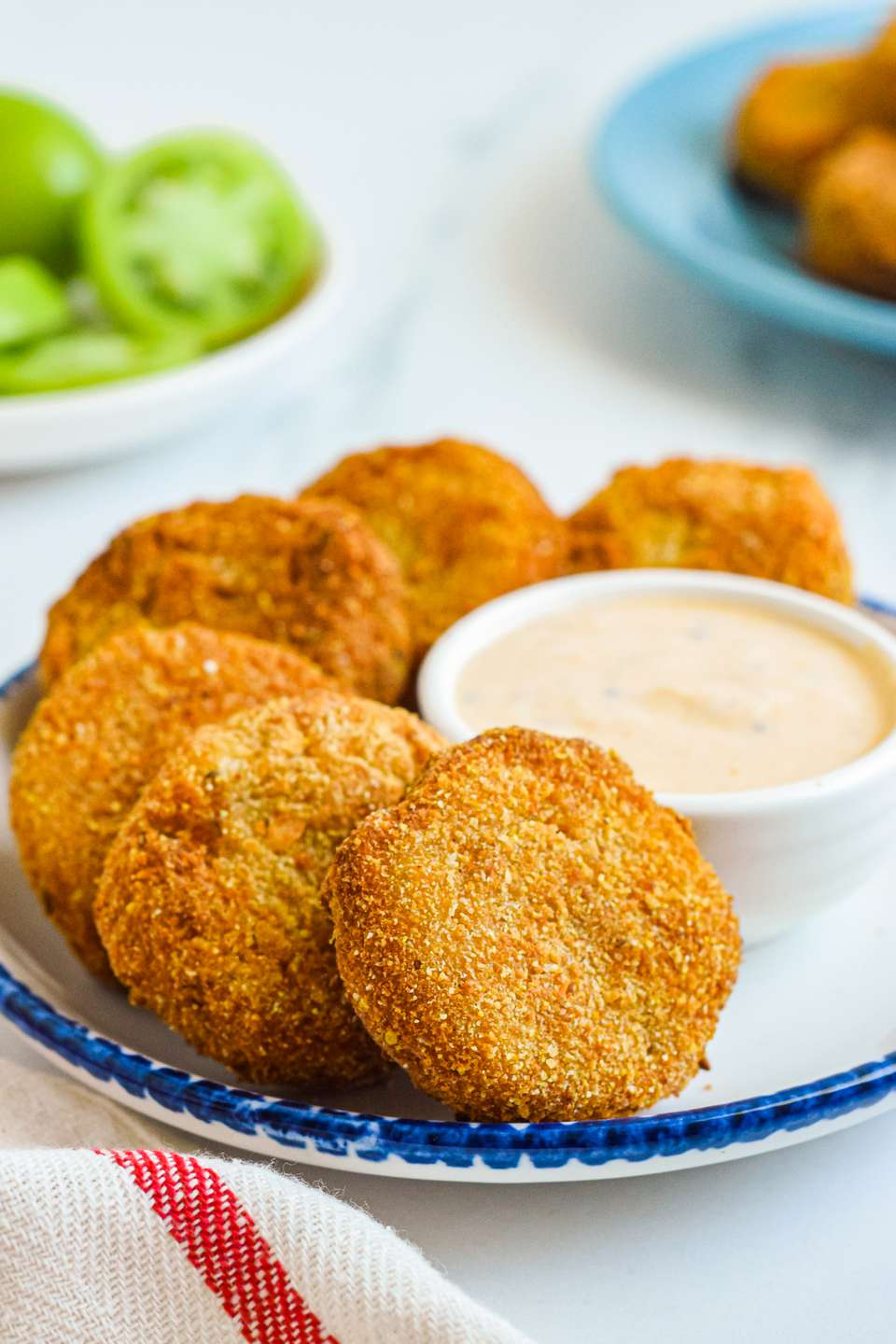 A plate of fried green tomatoes set next to a bowl of dip.