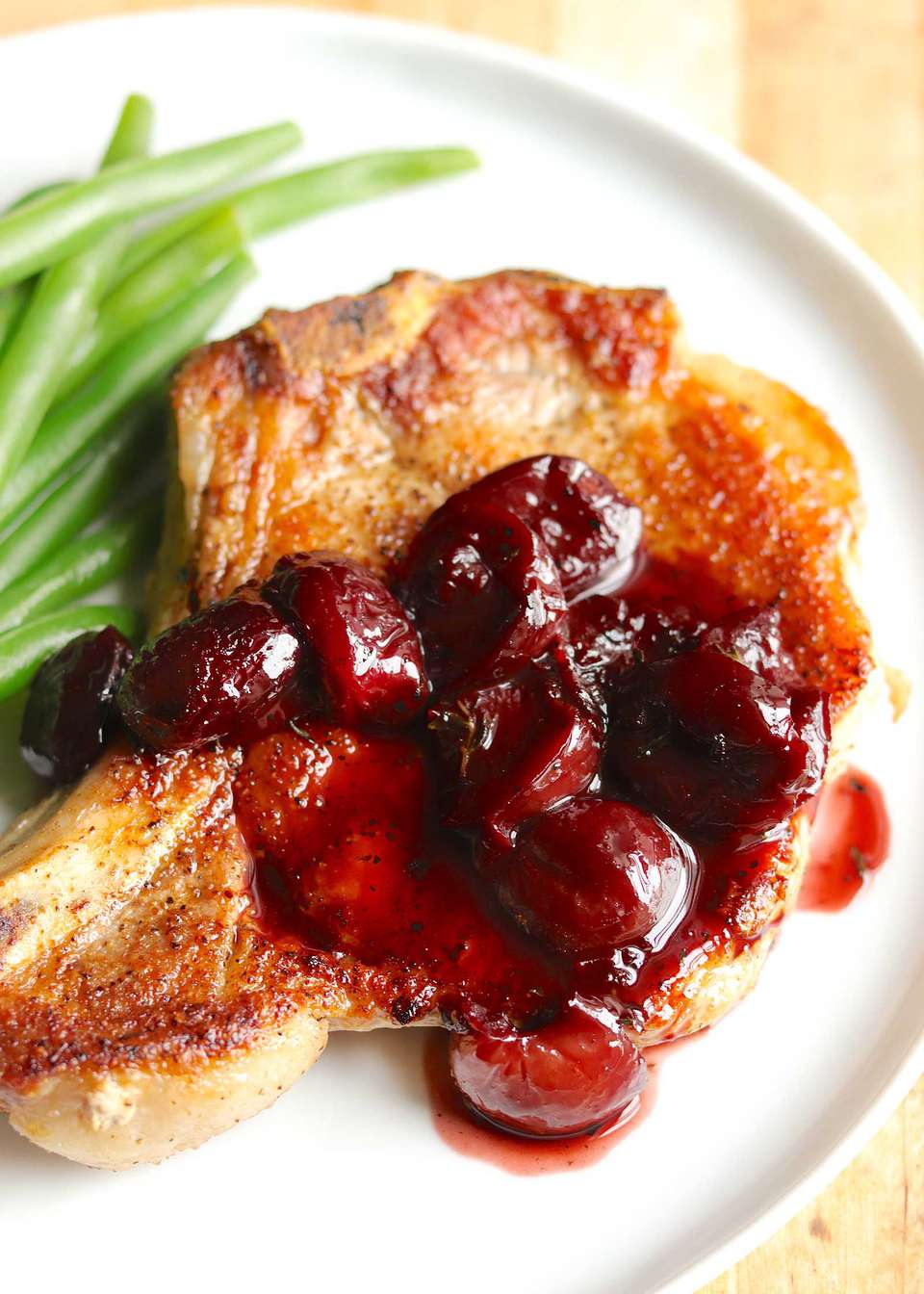 Close up of the bone-in pork chop topped with cherry pan sauce.