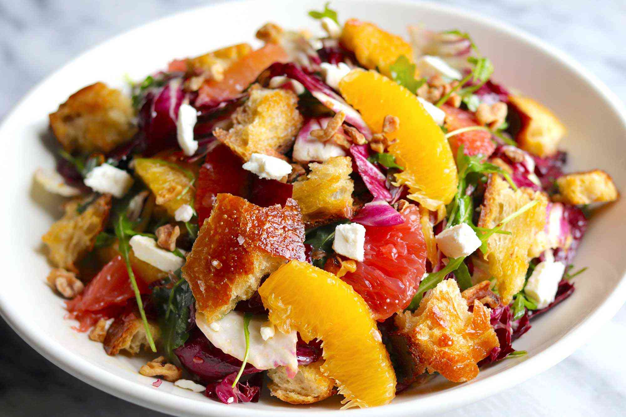 Side view of a winter salad in a white, wide bowl. Supremed orange and grapefruit, radicchio, croutons and feta cheese crumbles are visible.