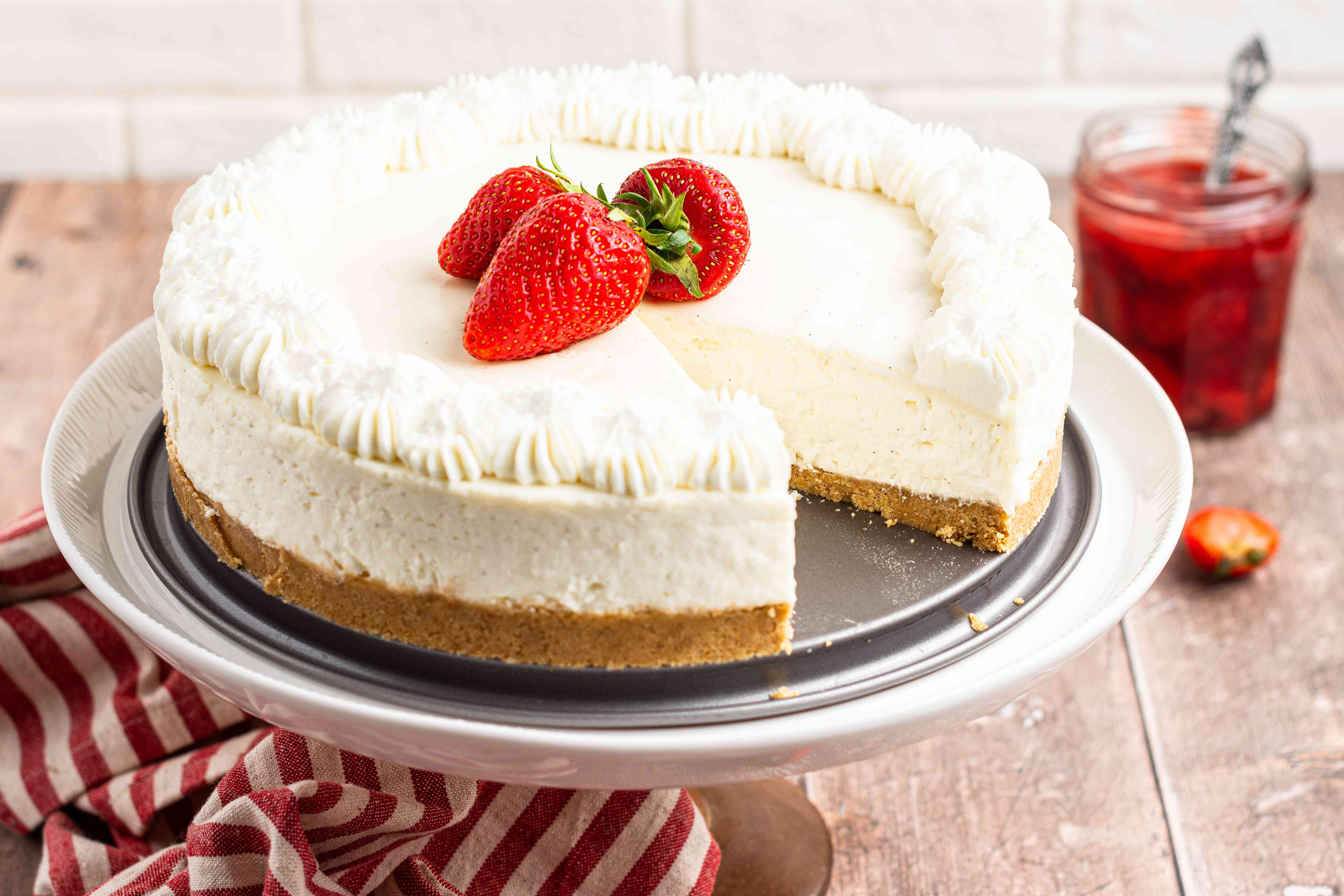 A cake stand with No bake cheesecake topped with fresh strawberries with a slice removed.