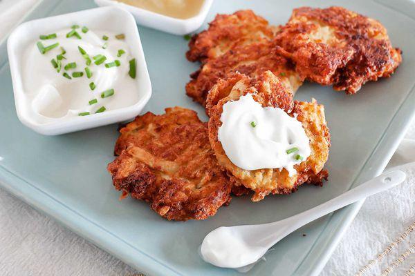 the best potato latkes on a blue platter with sour cream