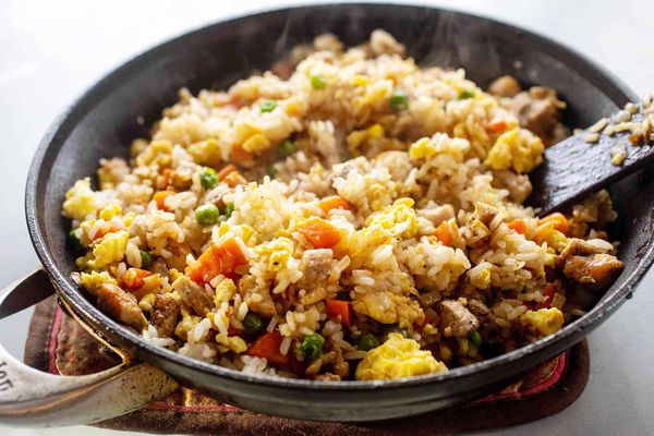A black skillet with prepared pork fried rice recipe inside. Steam is coming up from the dish and a spatula is resting in the rice on the left side.