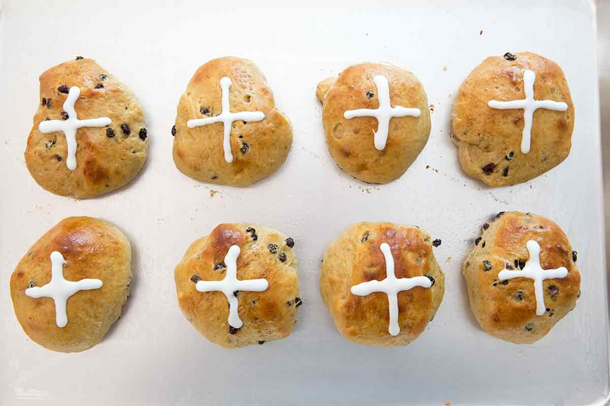 Two rows of Easter hot crossed buns cooling on a sheet pan