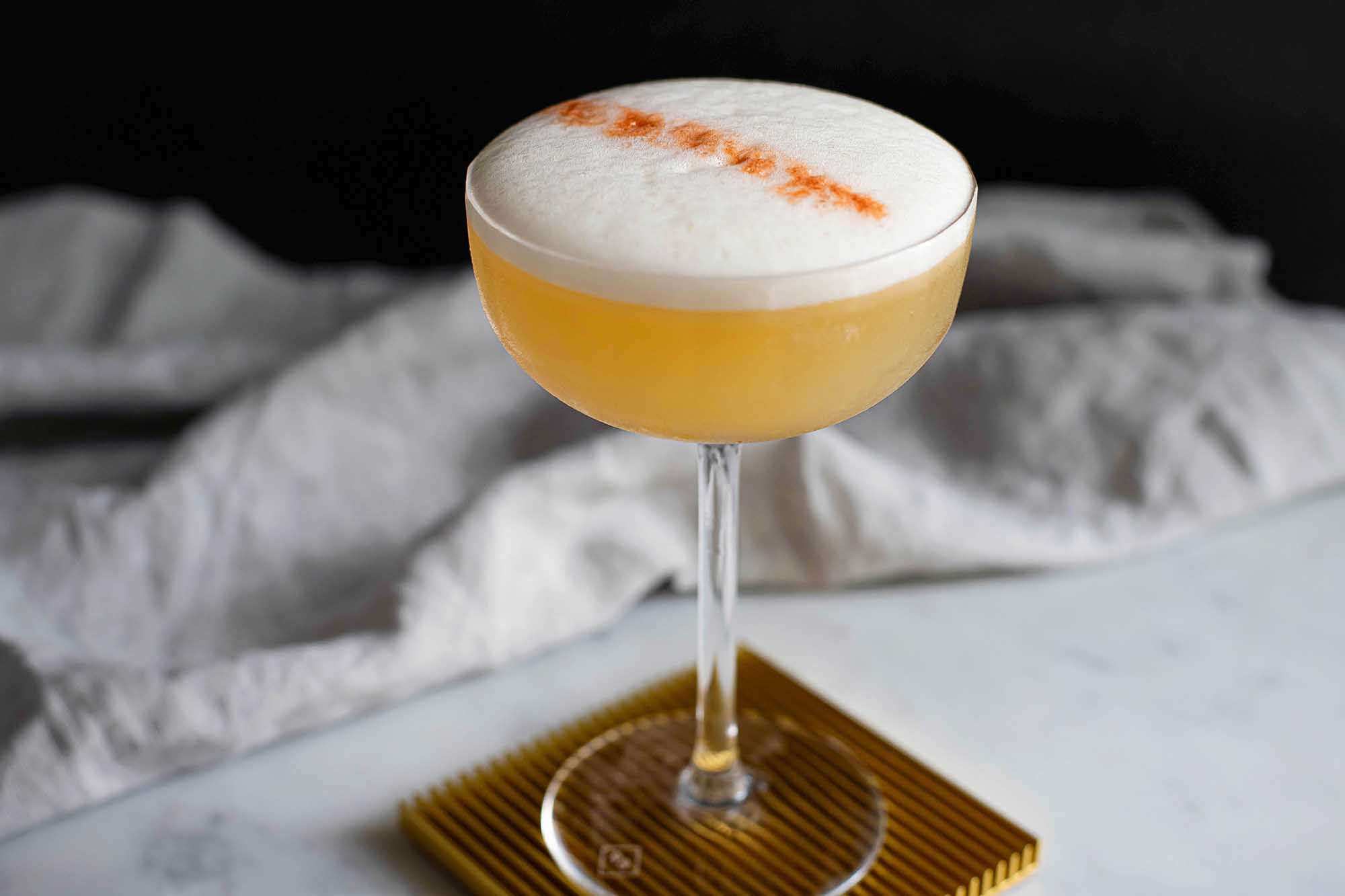 Whiskey Sour straight up in a glass with foam