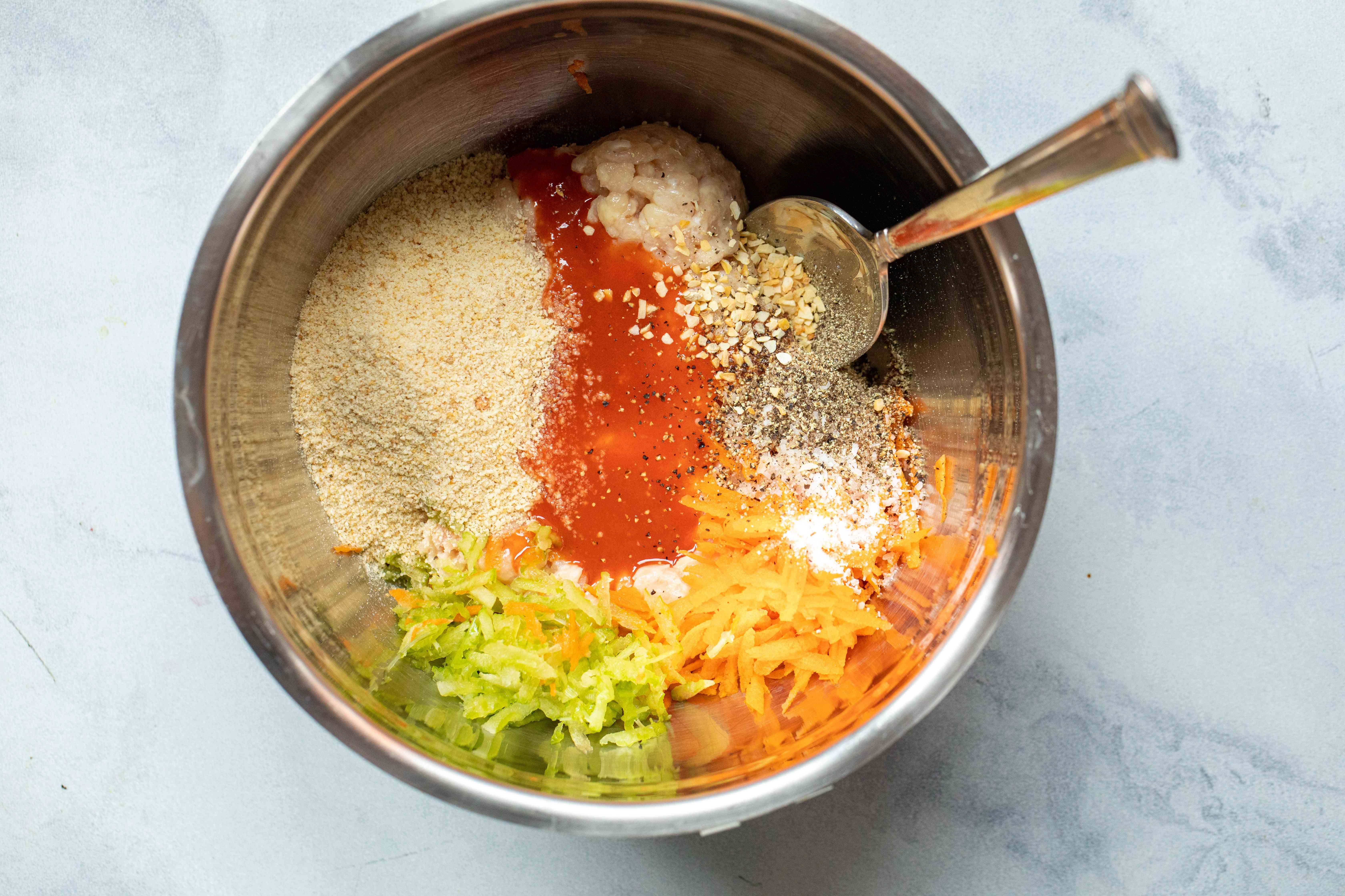 A metal bowl with ingredients to make buffalo chicken burgers.