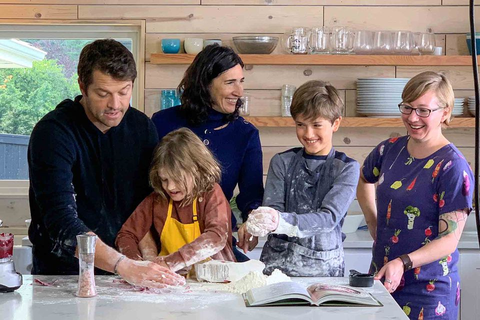 Misha and Vicki Collins with their kids and Emma Christensen making gnocchi