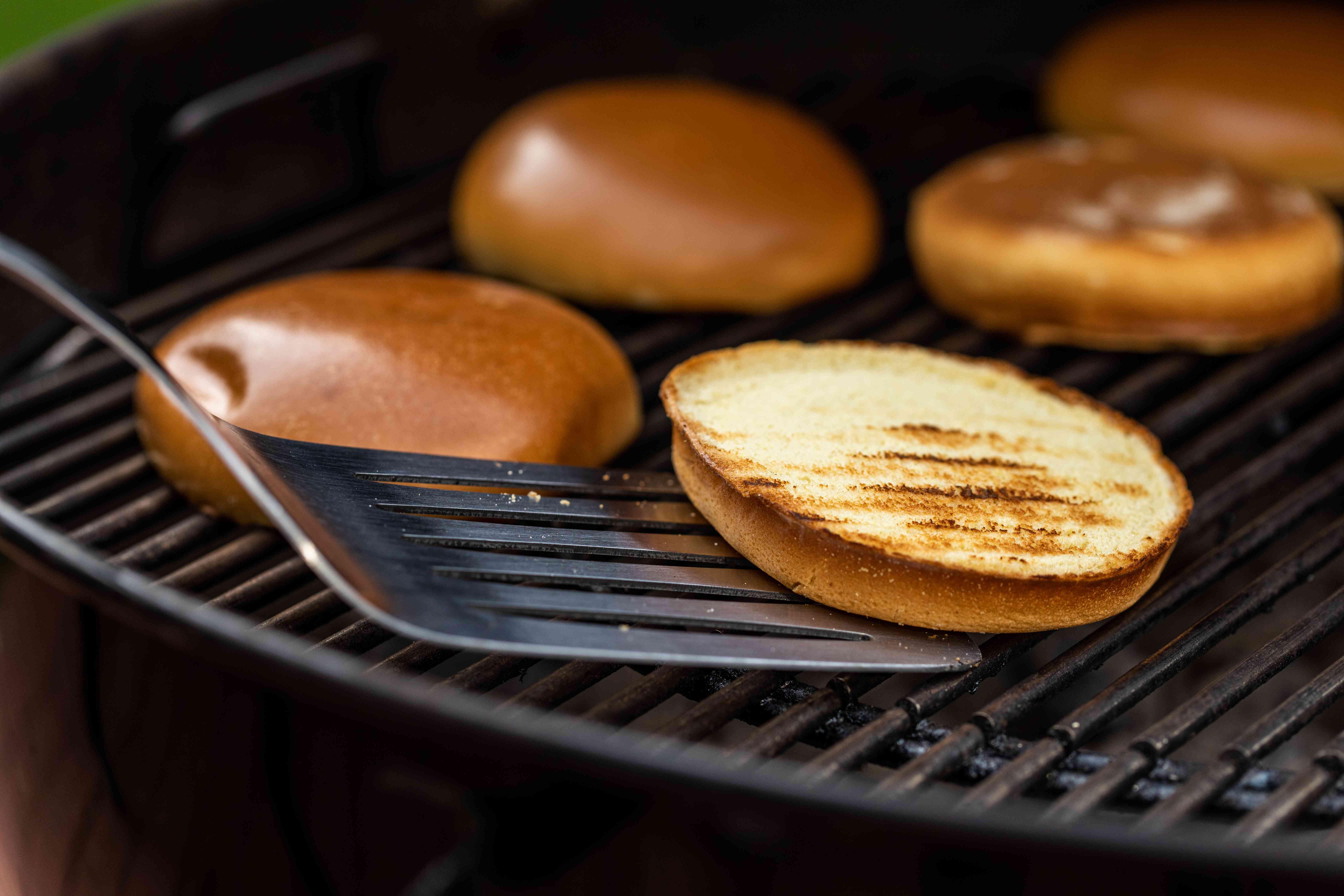 Spatula with a toasted hamburger bun on a grill.