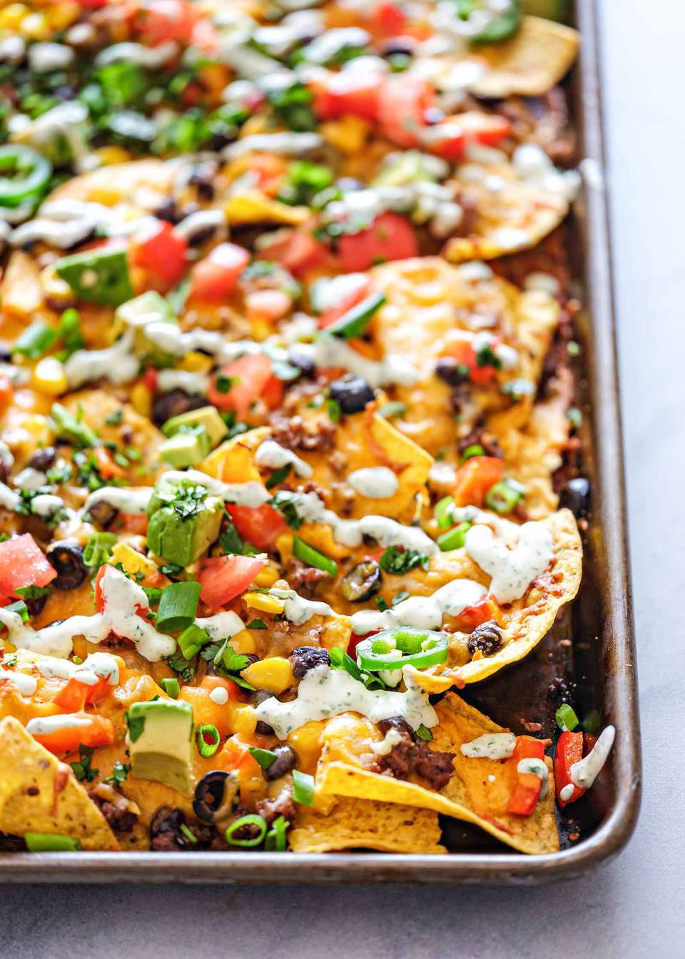 A pan of sheet pan nachos topped with spring onions