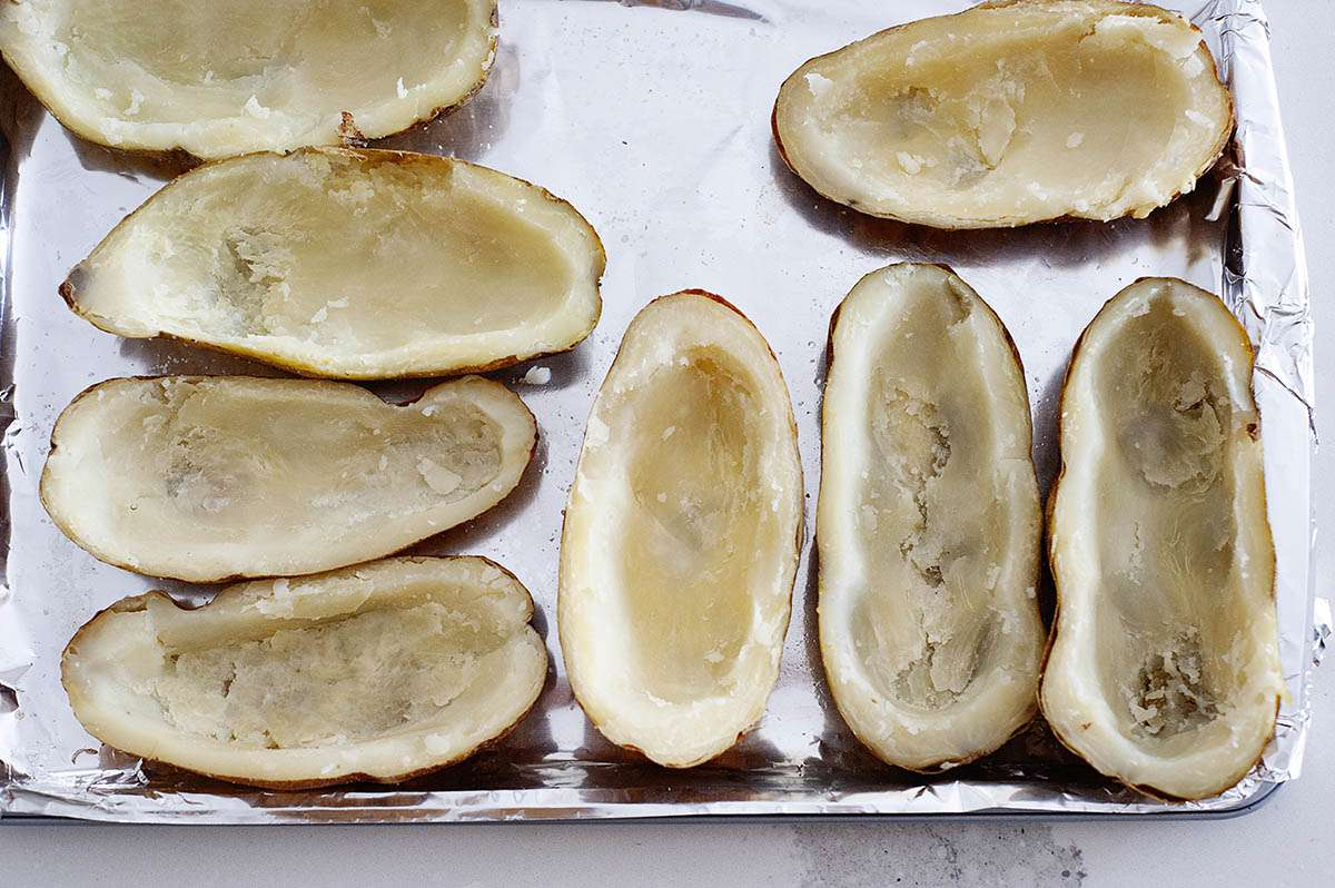 Baked potatoes on foil-lined baking sheet with the insides scooped out to make twice baked potatoes.