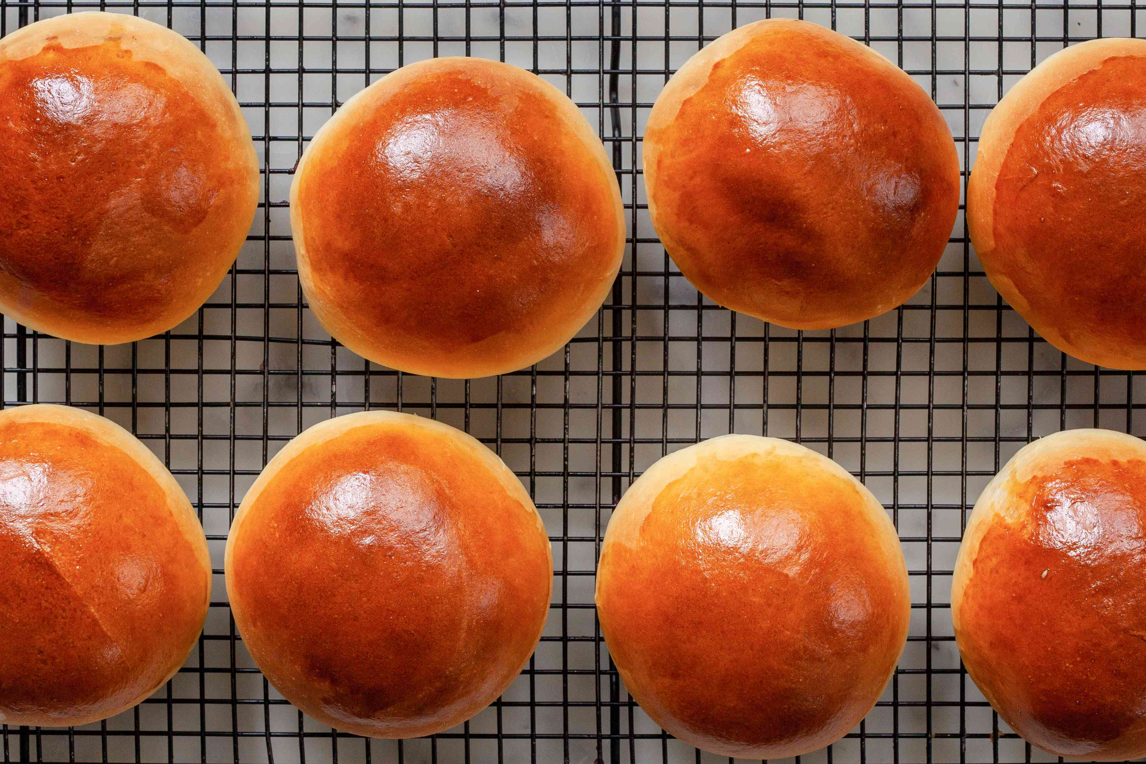 Overhead view of burger buns cooling on a rack.