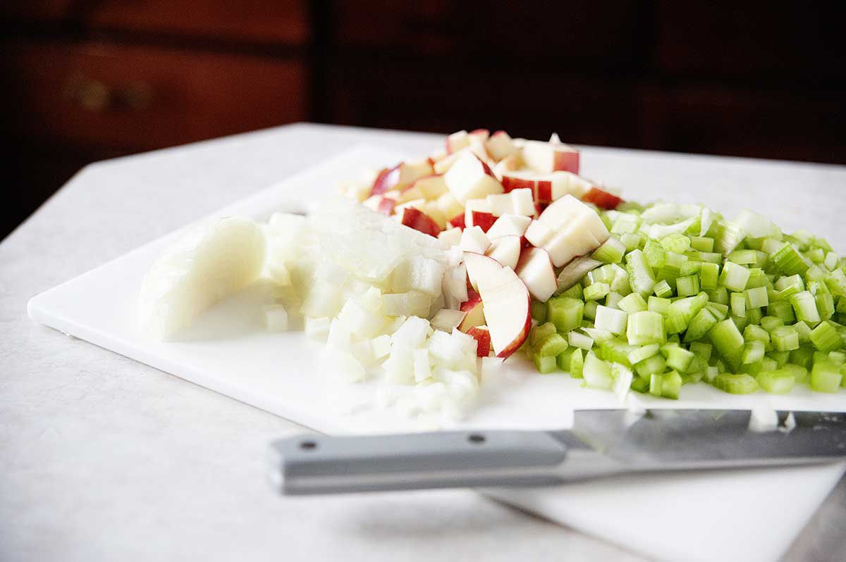 Apples, onions, and celery on diced on a cutting board for easy thanksgiving stuffing.
