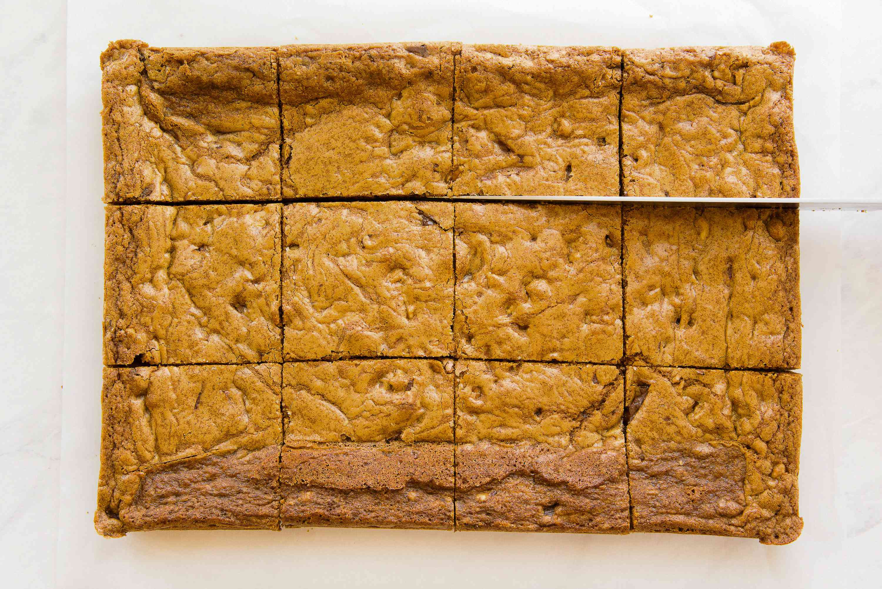 Slicing chocolate chip cookie bars into squares.