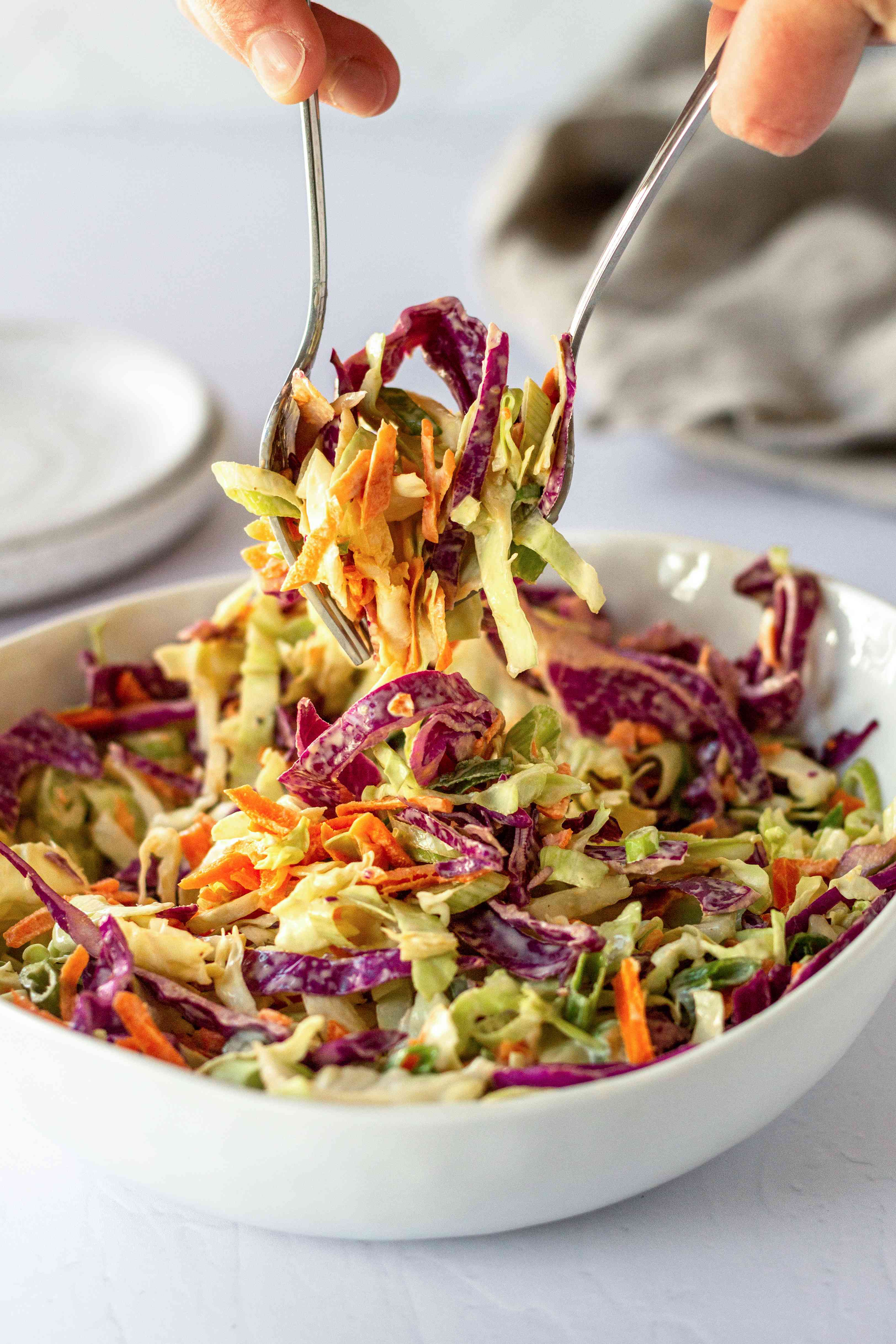 Forks lifting bright cabbage coleslaw out of a white bowl.