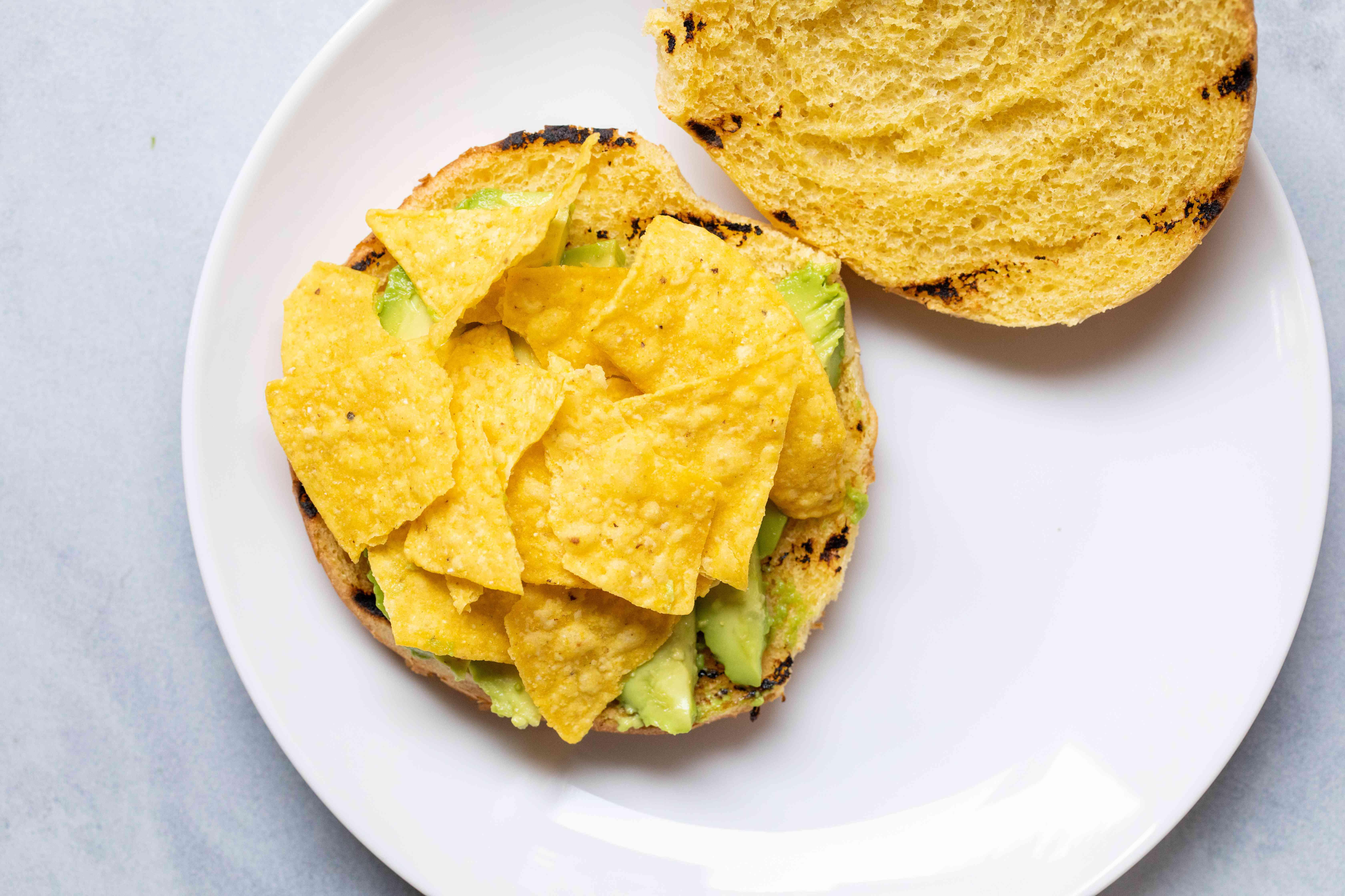 A toasted bun topped with avocado and tortilla chips on a plate to make an Avocado burger.