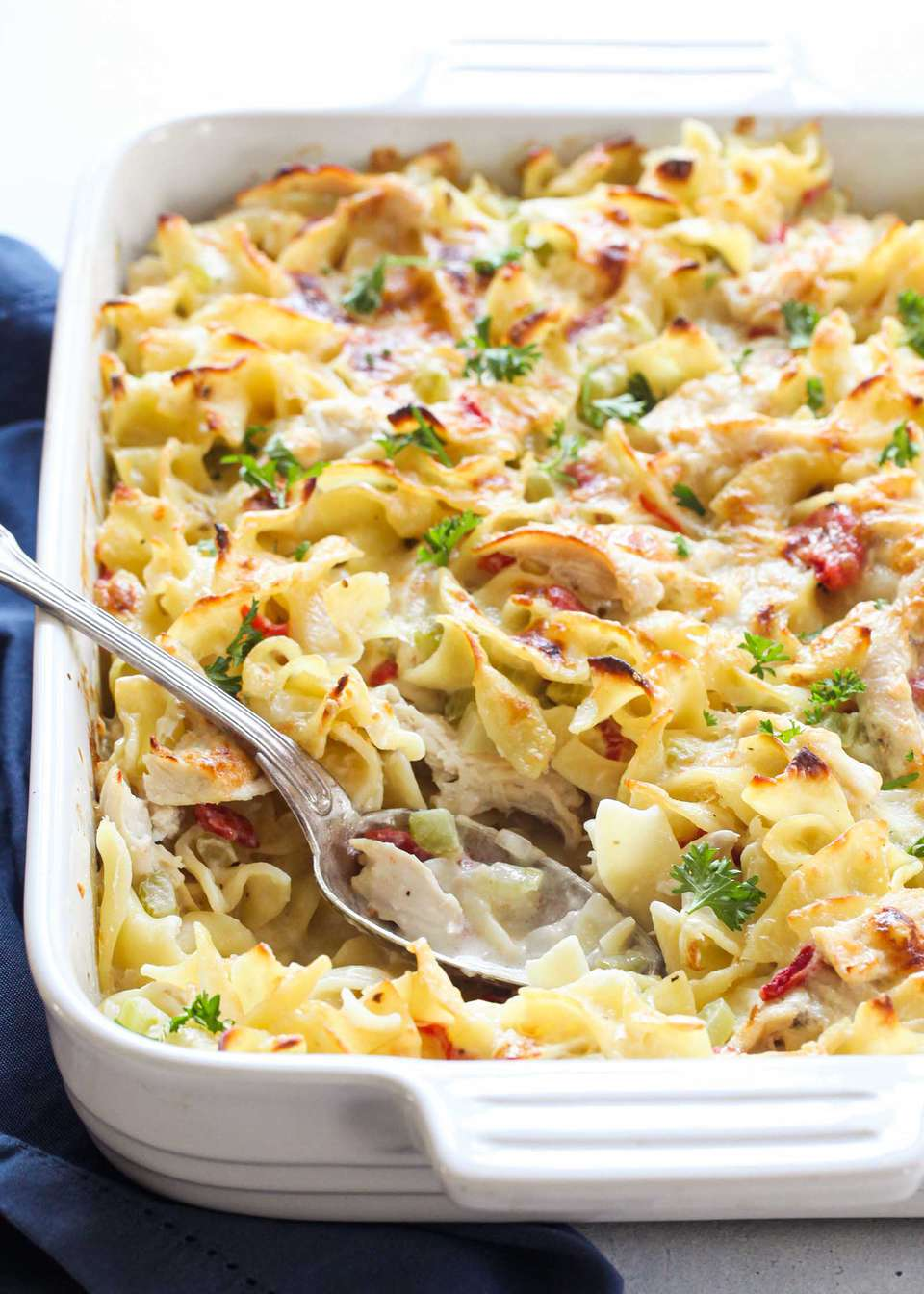 Creamy Chicken Noodle Casserole in a white baking dish with a silver spoon.