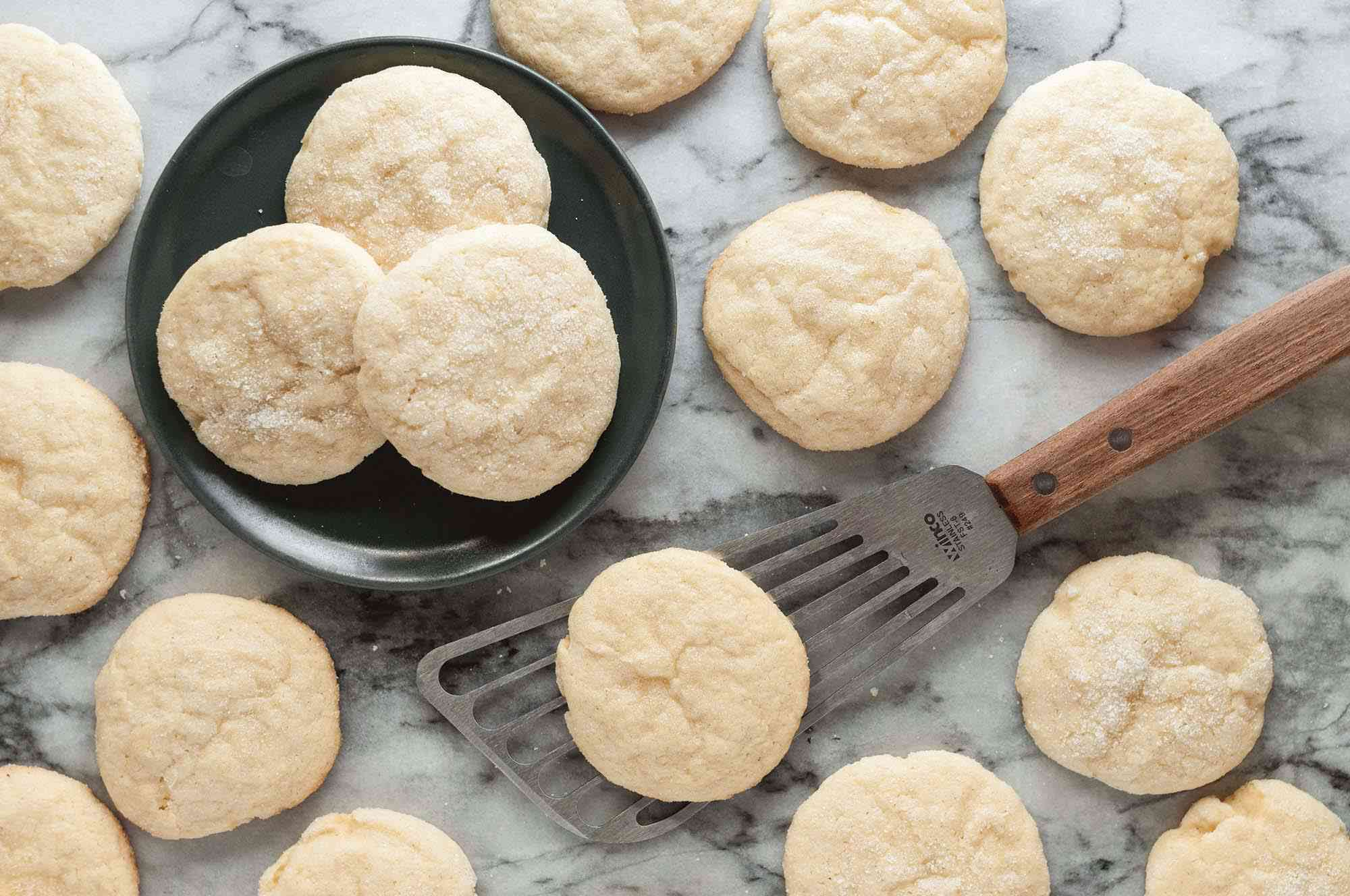 soft lemon cookies on plate and counter with spatula