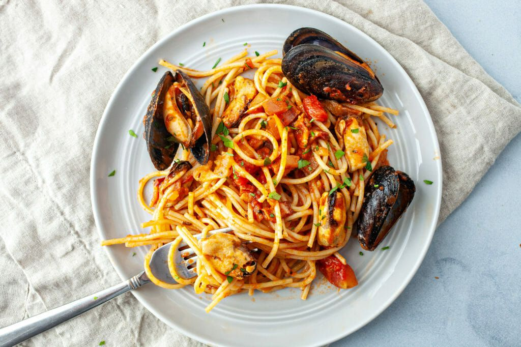 Mussels in tomato sauce recipe - plate of spaghetti with mussels on side and fork