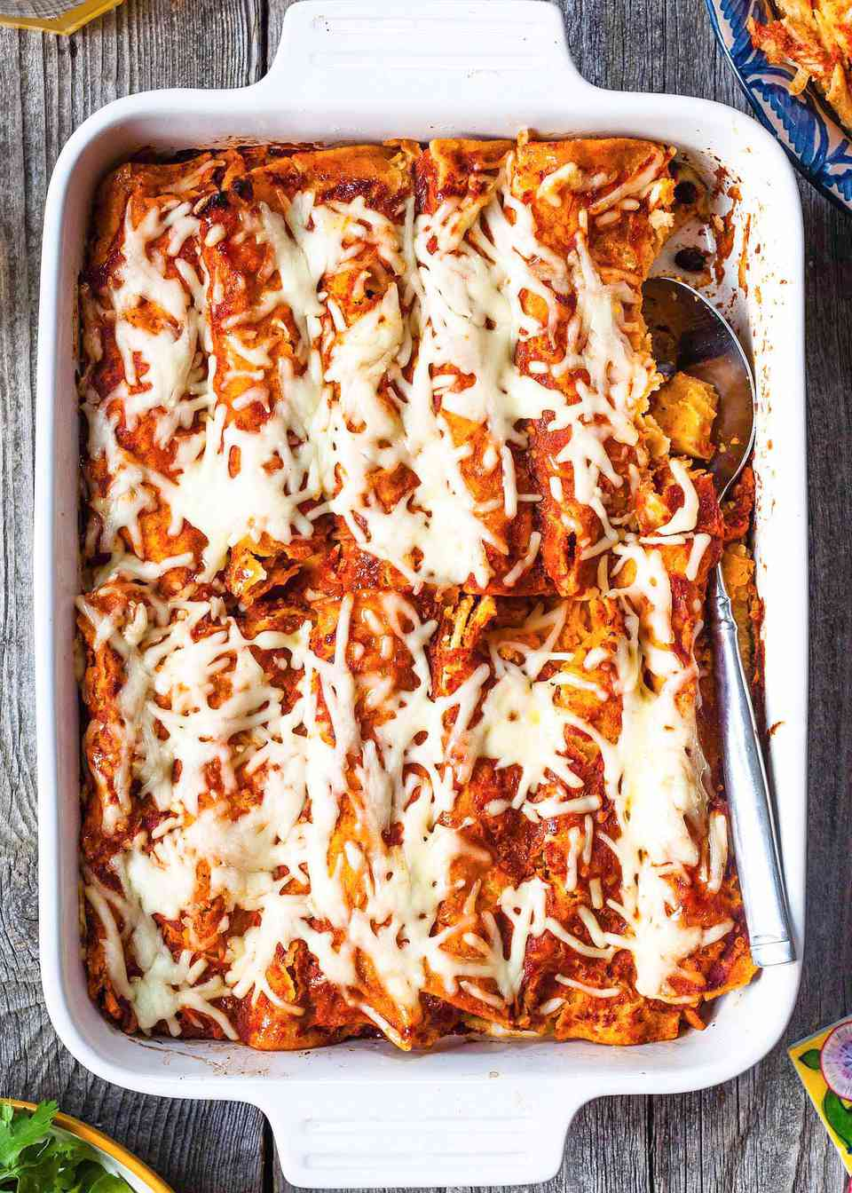 Casserole dish filled with homemade vegetairan enchiladas fillled iwth butternut squash and topped with cheese