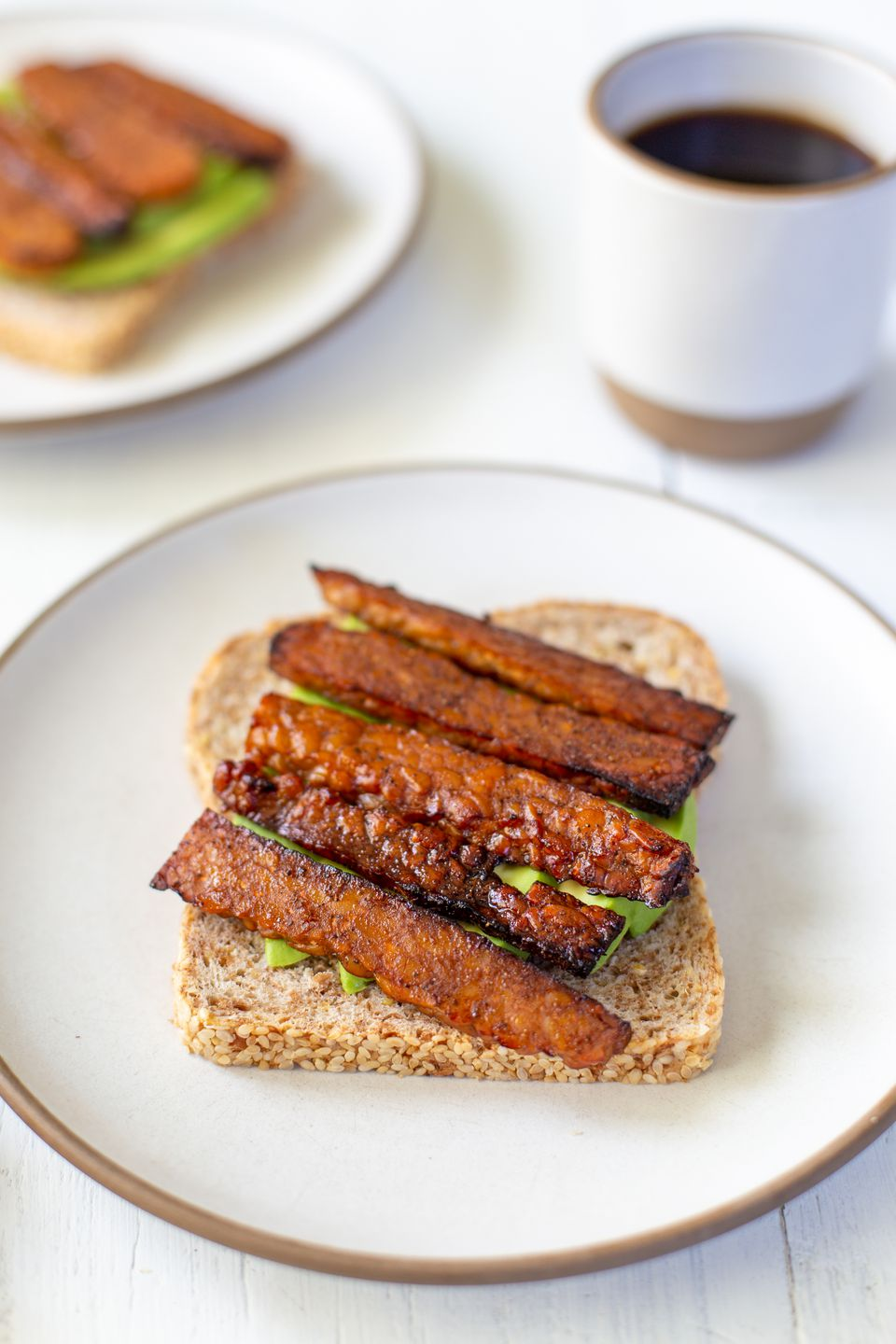 Vegan Bacon on toast with avocado underneath it and a second plate and a cup of coffee behind it.
