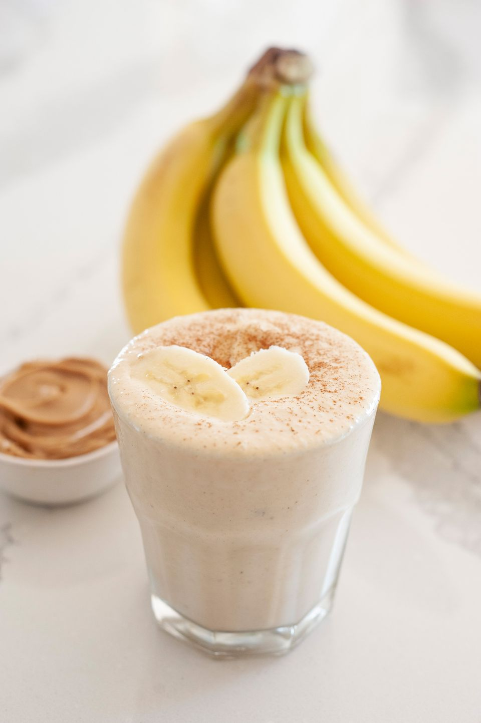 Simple peanut butter banana smoothie topped with sliced bananas and a bunch of bananas and a small container of peanut butter behind it.