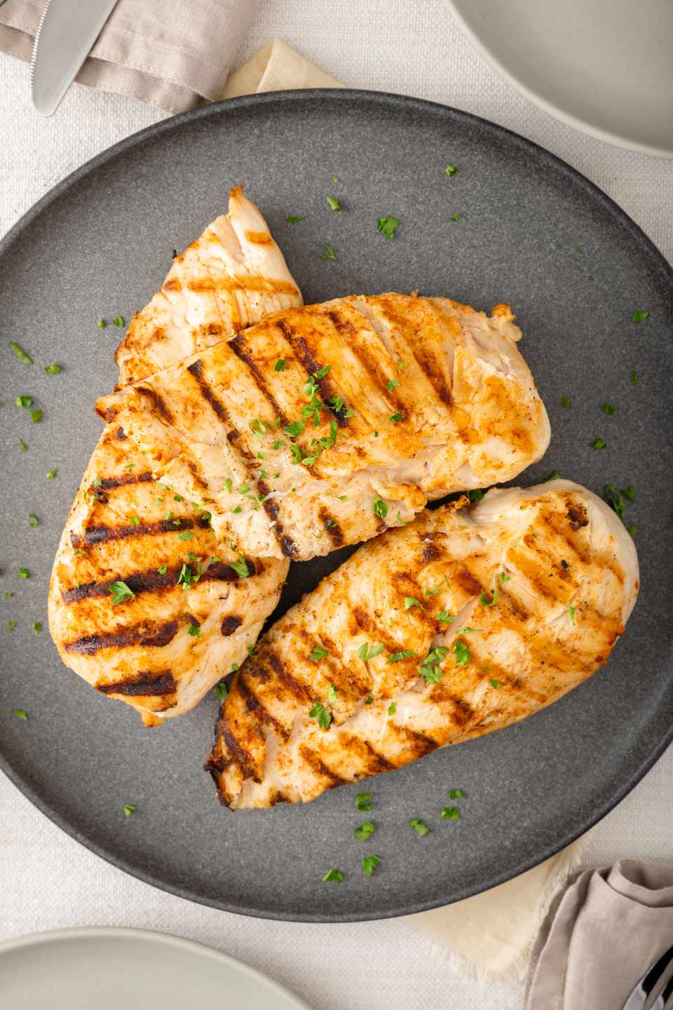 Overhead view of grilled and brined chicken on a plate.