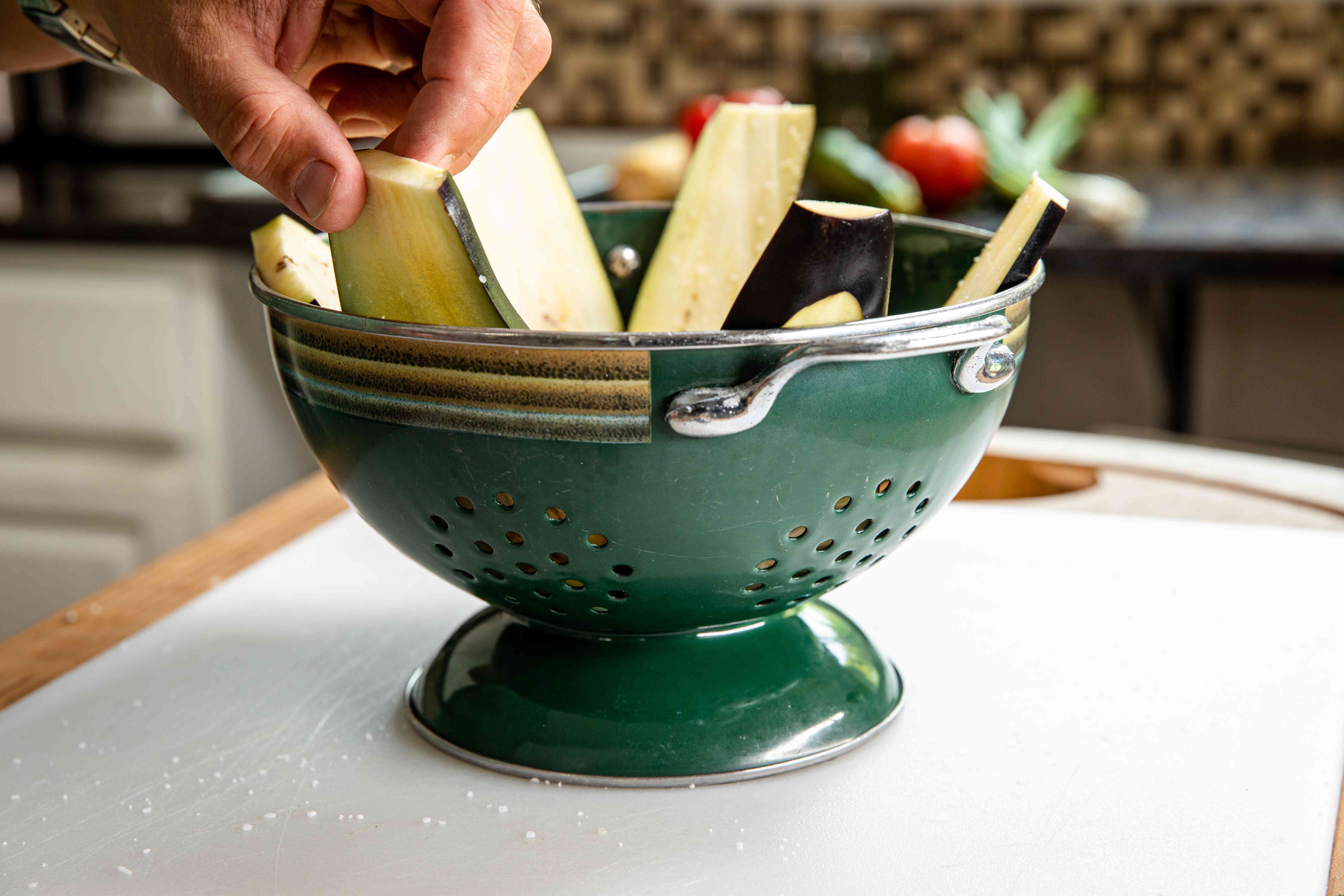 Setting eggplant slices in a colander to make easy grilled vegetable nachos.