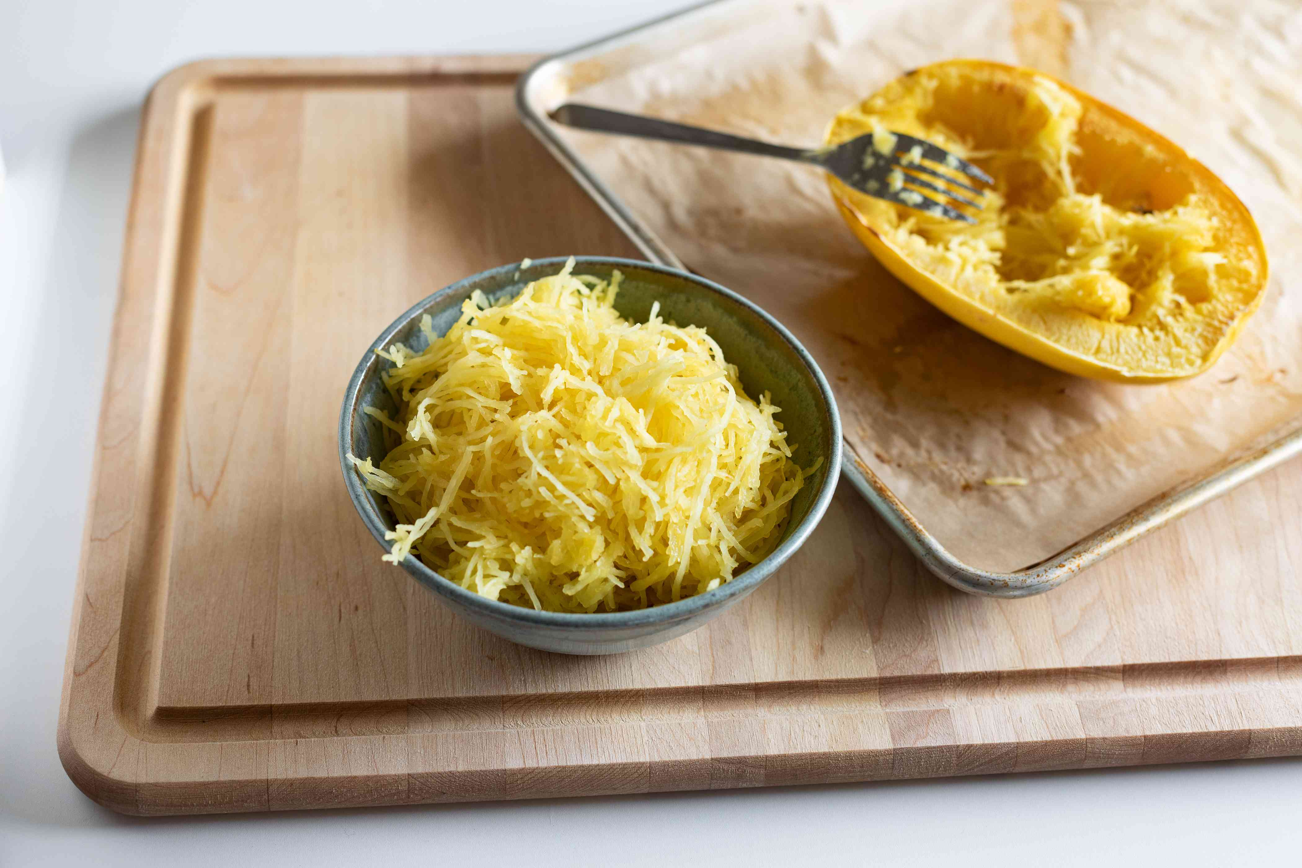 Roasted spaghetti squash in a bowl next to whole squash on sheet pan