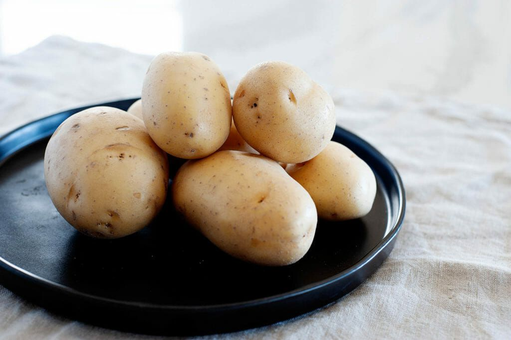 Side view of a stack of yellow potatoes on a tray.