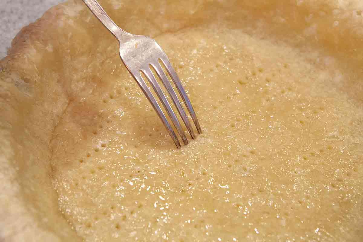 prick the bottom of the half baked pie crust with the tines of a fork