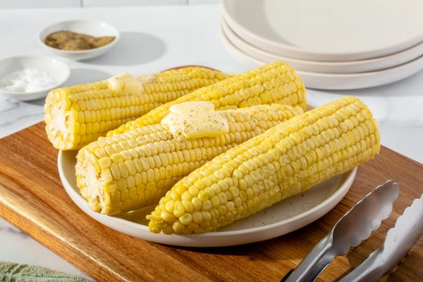 A plate of microwave corn on the cob set on a cutting board and topped with butter.