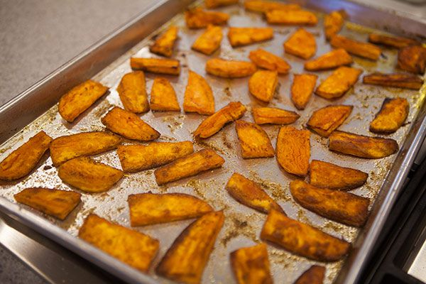 How to bake sweet potatoes by spreading on a baking sheet.