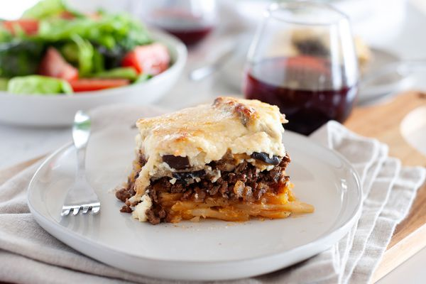 A piece of eggplant moussaka on a plate with a glass of wine and a salad behind it.