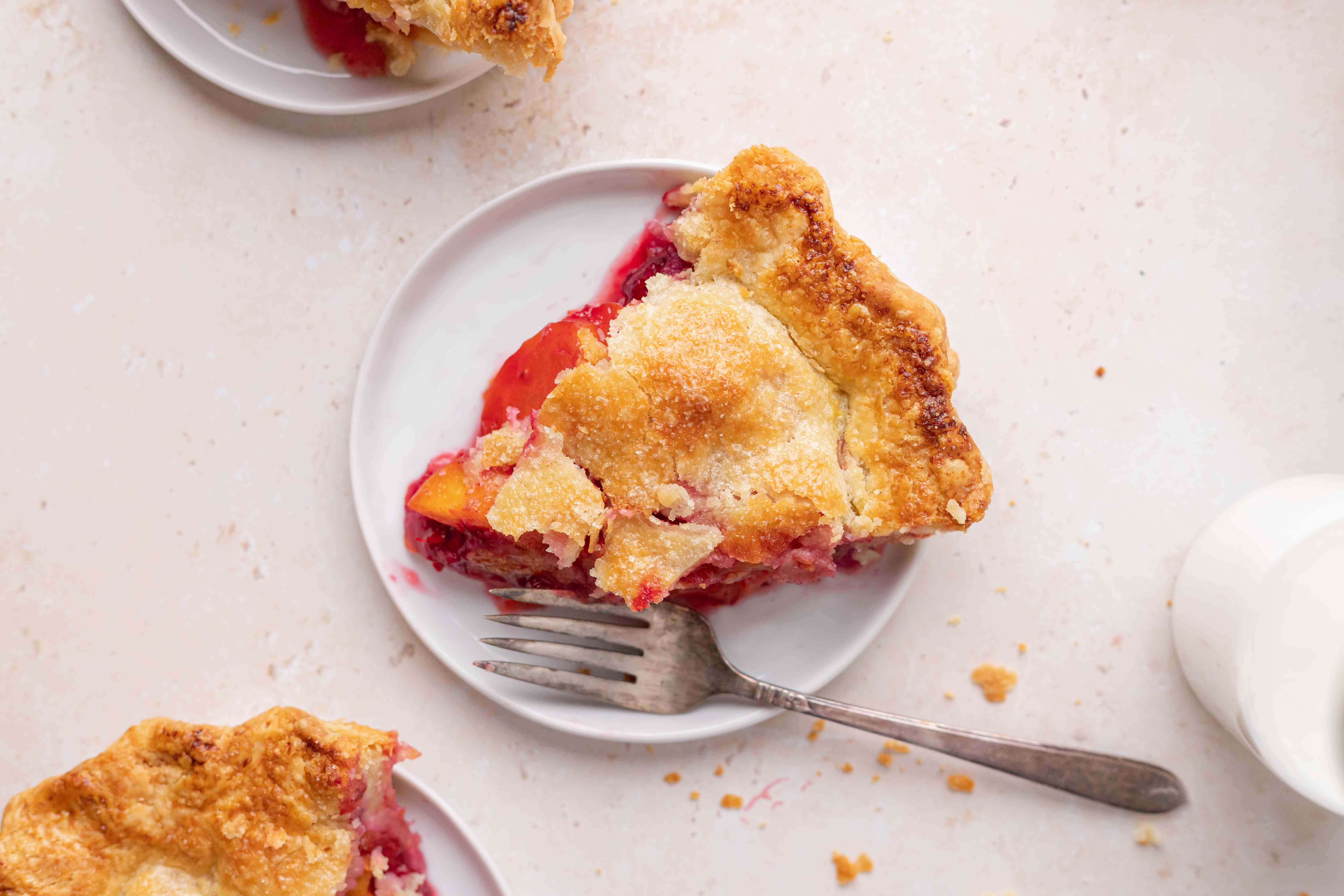Overhead view of a slice of stone fruit and berry pie.