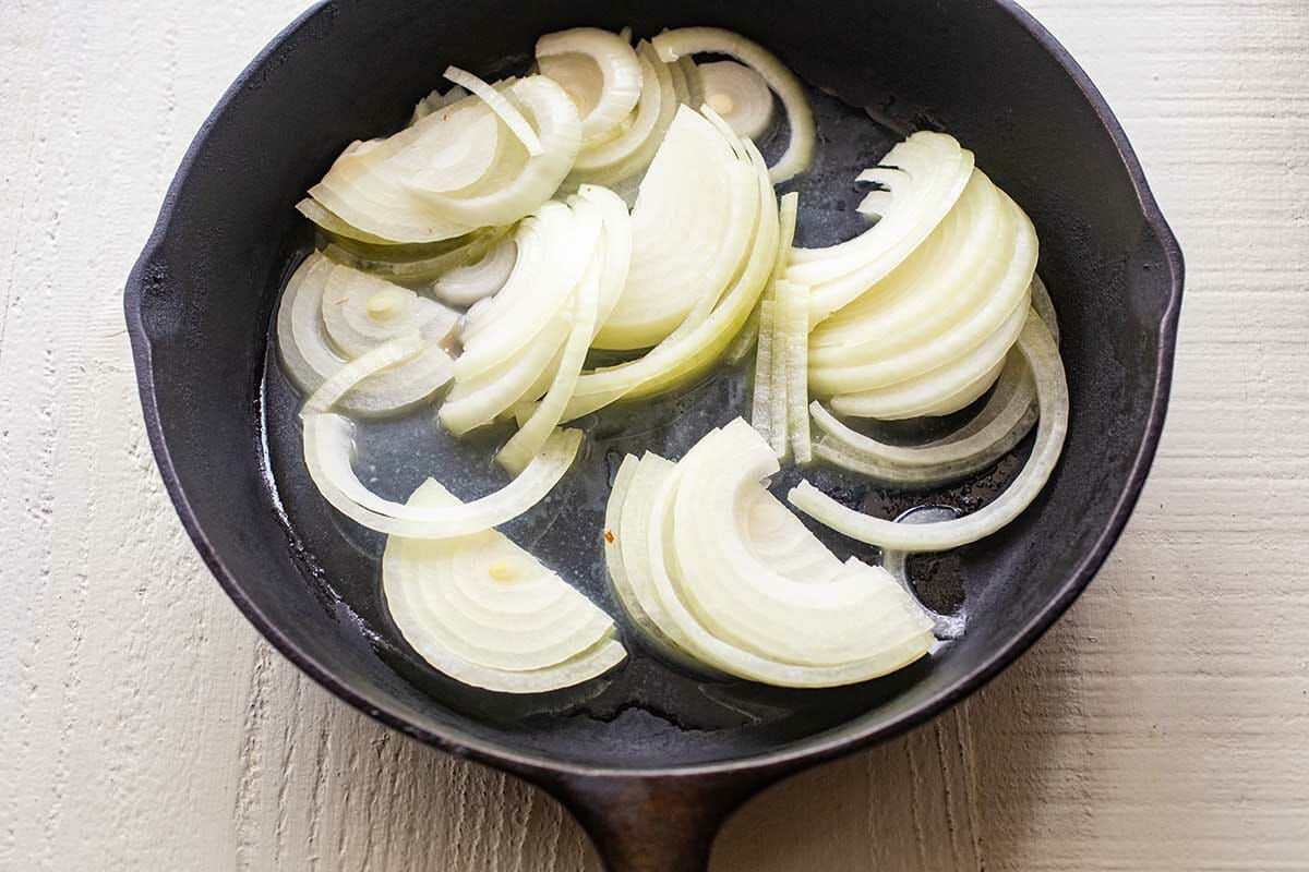 A cast iron skillet with sliced onions to show how to make a patty melt.
