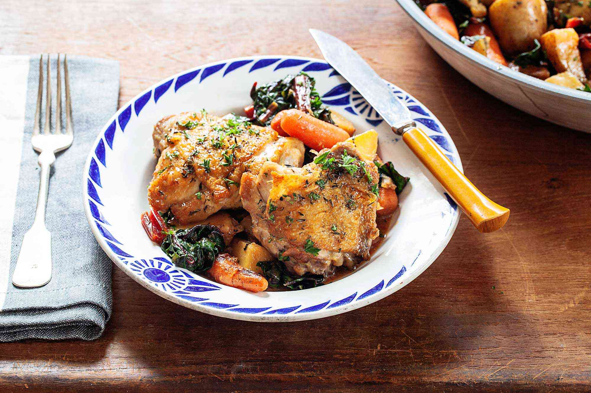 Two crispy skillet chicken thighs with baby carrots and wilted greens. The shallow bowl has a blue pattern around the edge. A yellow handled knife is on the right edge. A folded napkin has a fork on top. More of the skillet chicken thighs with potatoes, carrots and greens in a bowl partially visible in the upper right corner.