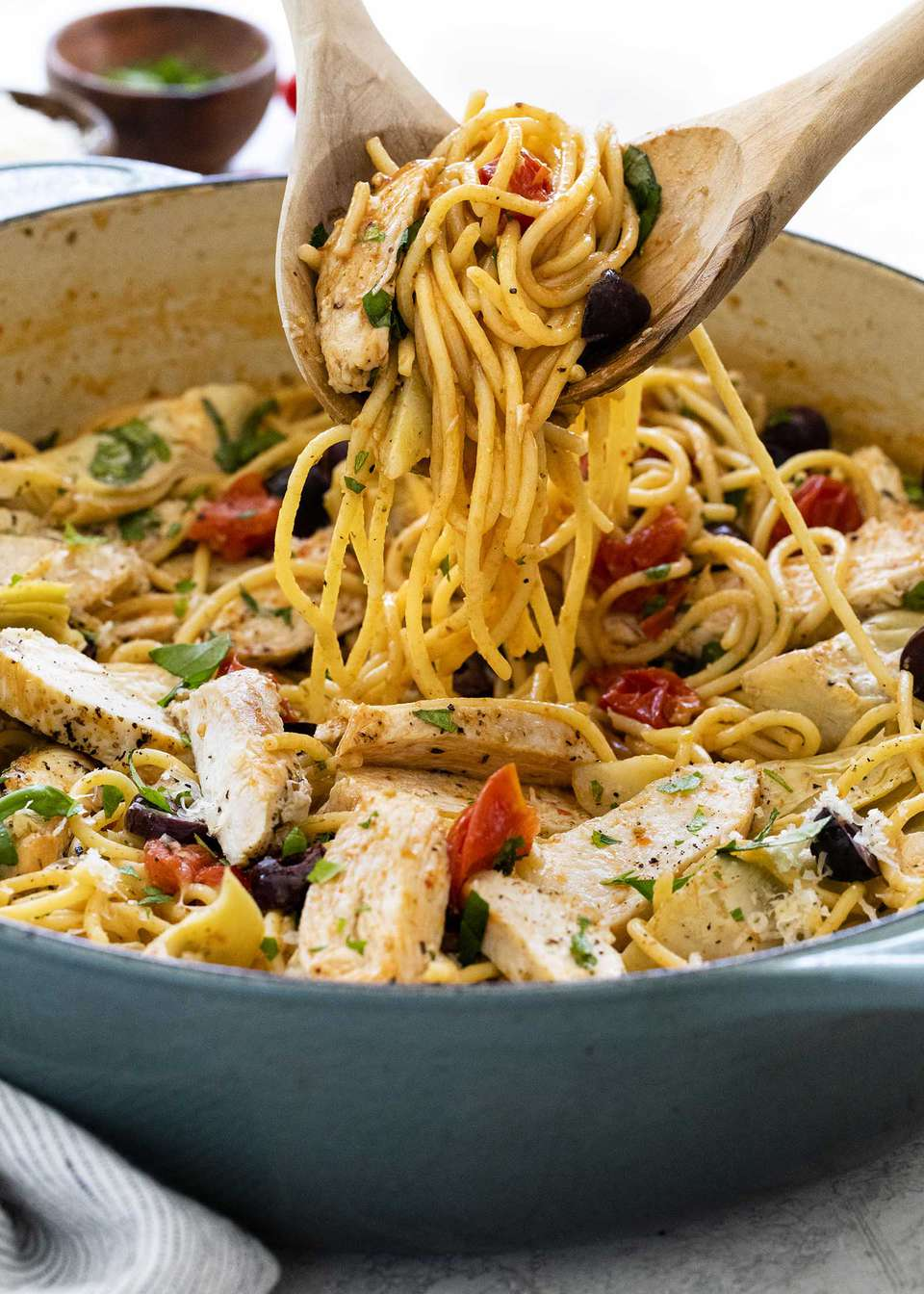 Two wooden spoons scoop easy chicken pasta skillet dinner out of a large skillet.