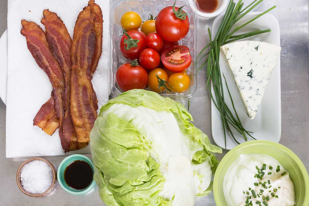 Ingredients for blue cheese wedge salad. Bacon, tomatoes, iceberg lettuce and blue cheese.