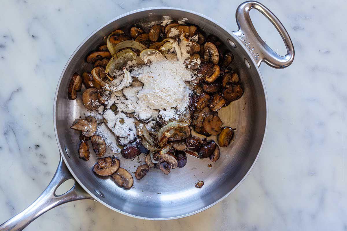 Mushrooms being sauteed in a silver skillet to make homemade vegetarian mushroom gravy