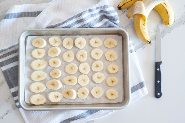 Slices of bananas on a half sheet pan ready for freezing
