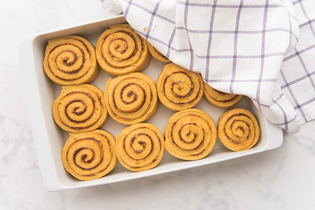 The Best Pumpkin Cinnamon Rolls partially covered in a baking dish.